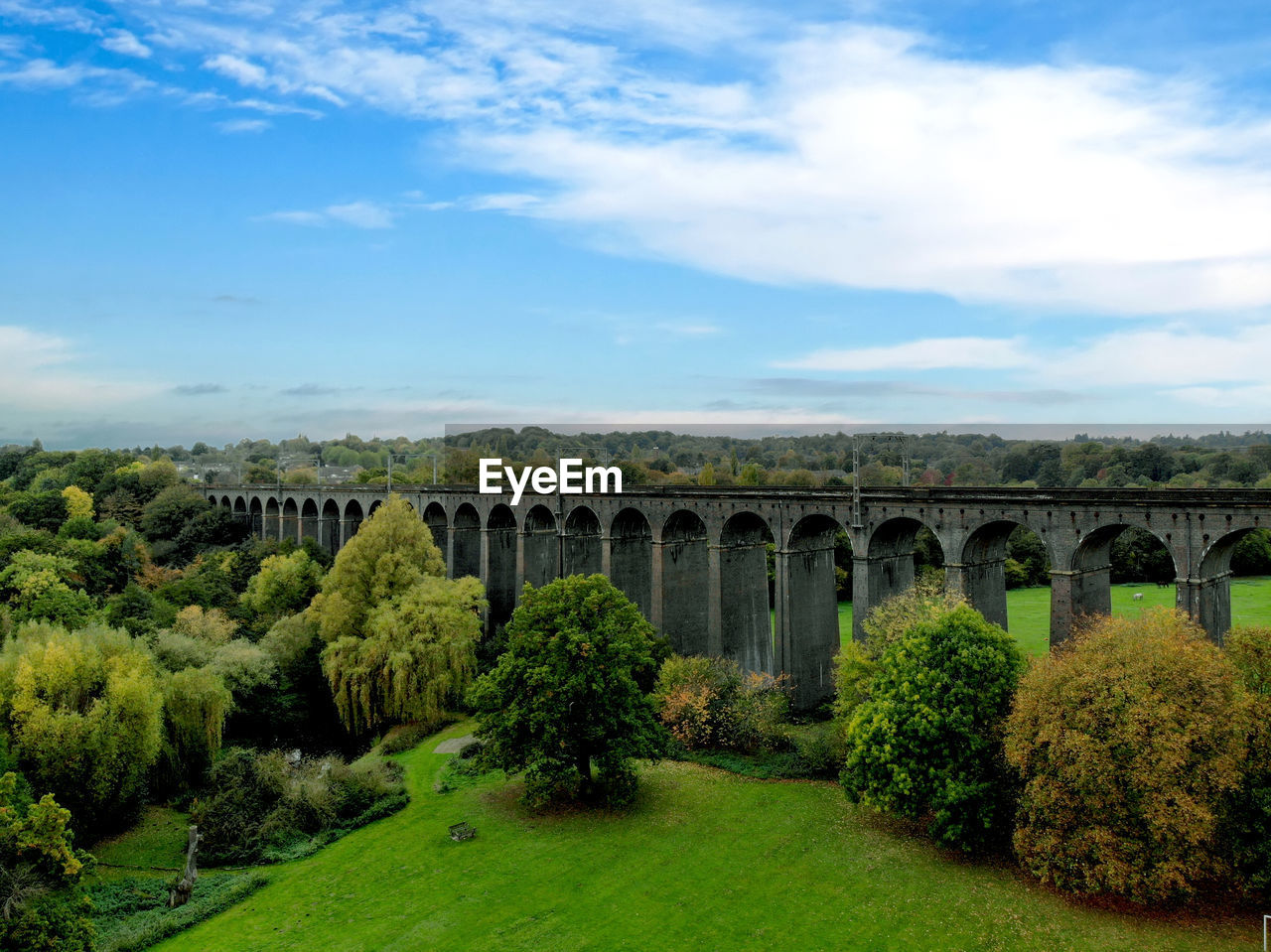 sky, cloud - sky, architecture, plant, built structure, nature, bridge, connection, bridge - man made structure, tree, arch, no people, transportation, green color, grass, day, viaduct, arch bridge, growth, beauty in nature, outdoors, architectural column