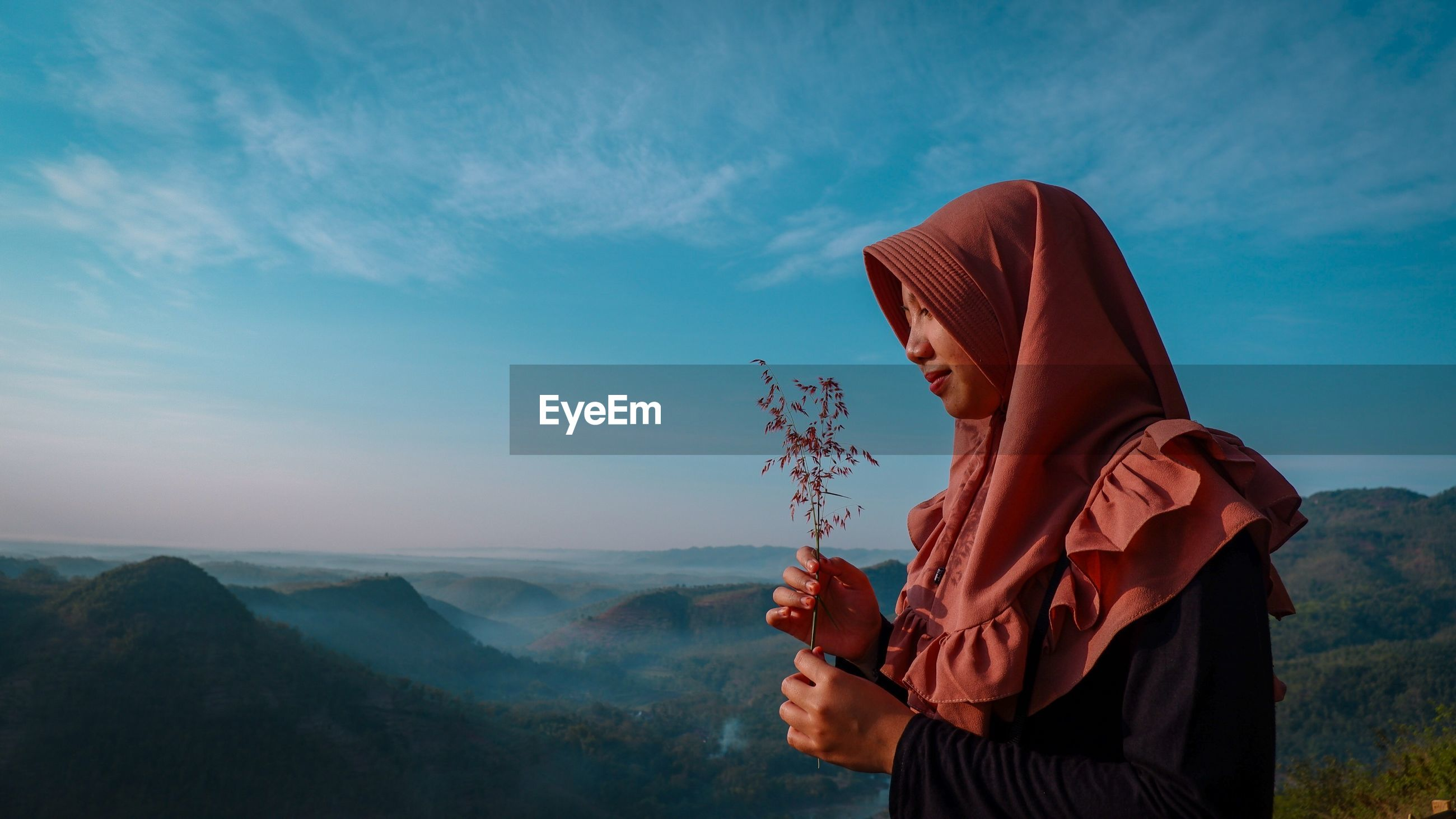 Side view of woman wearing headscarf while holding plant on mountain against sky