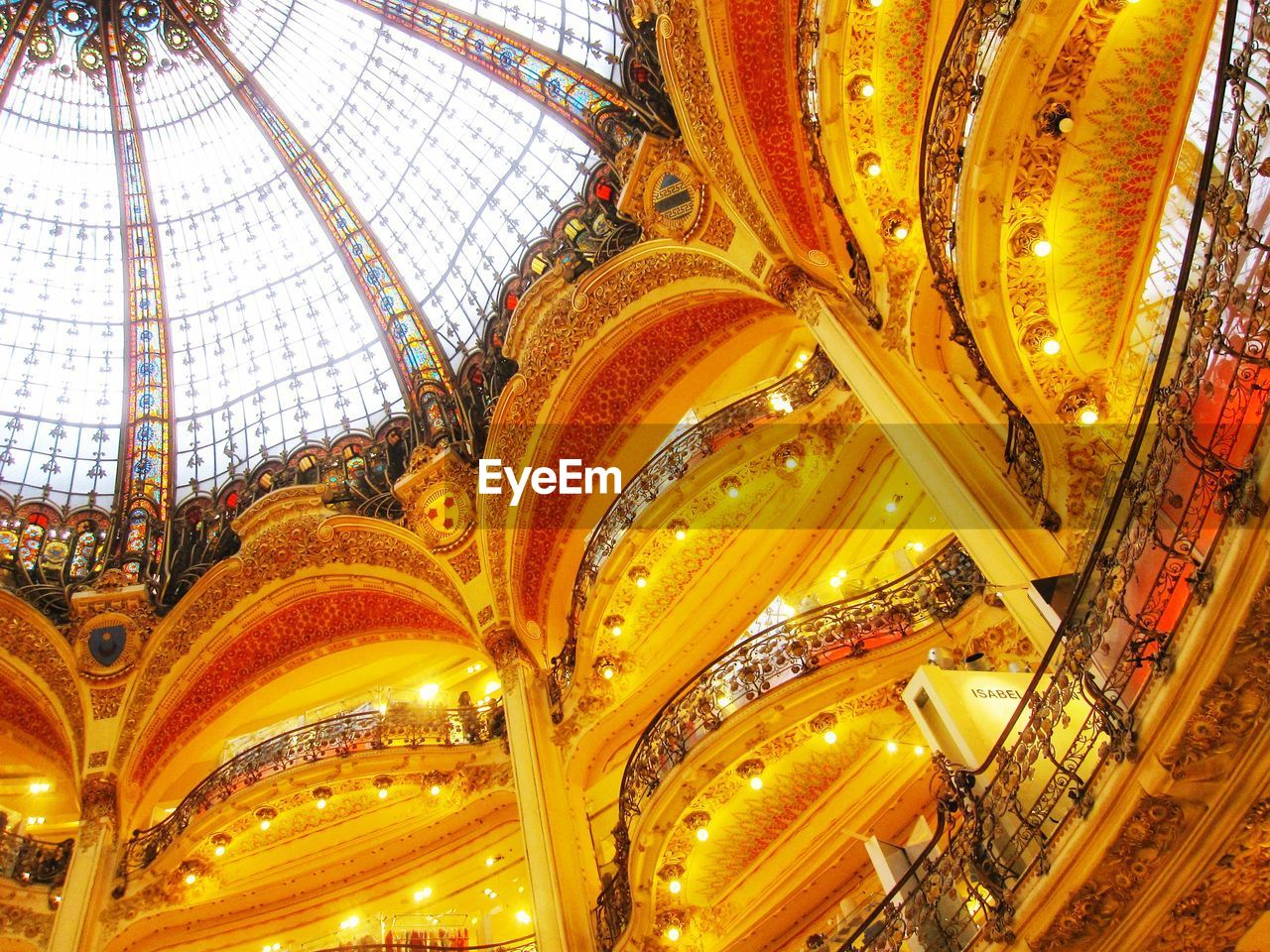 low angle view, ceiling, architecture, built structure, indoors, religion, illuminated, no people, lighting equipment, place of worship, building, belief, pattern, spirituality, design, gold colored, city, travel destinations, ornate, directly below, luxury, architecture and art