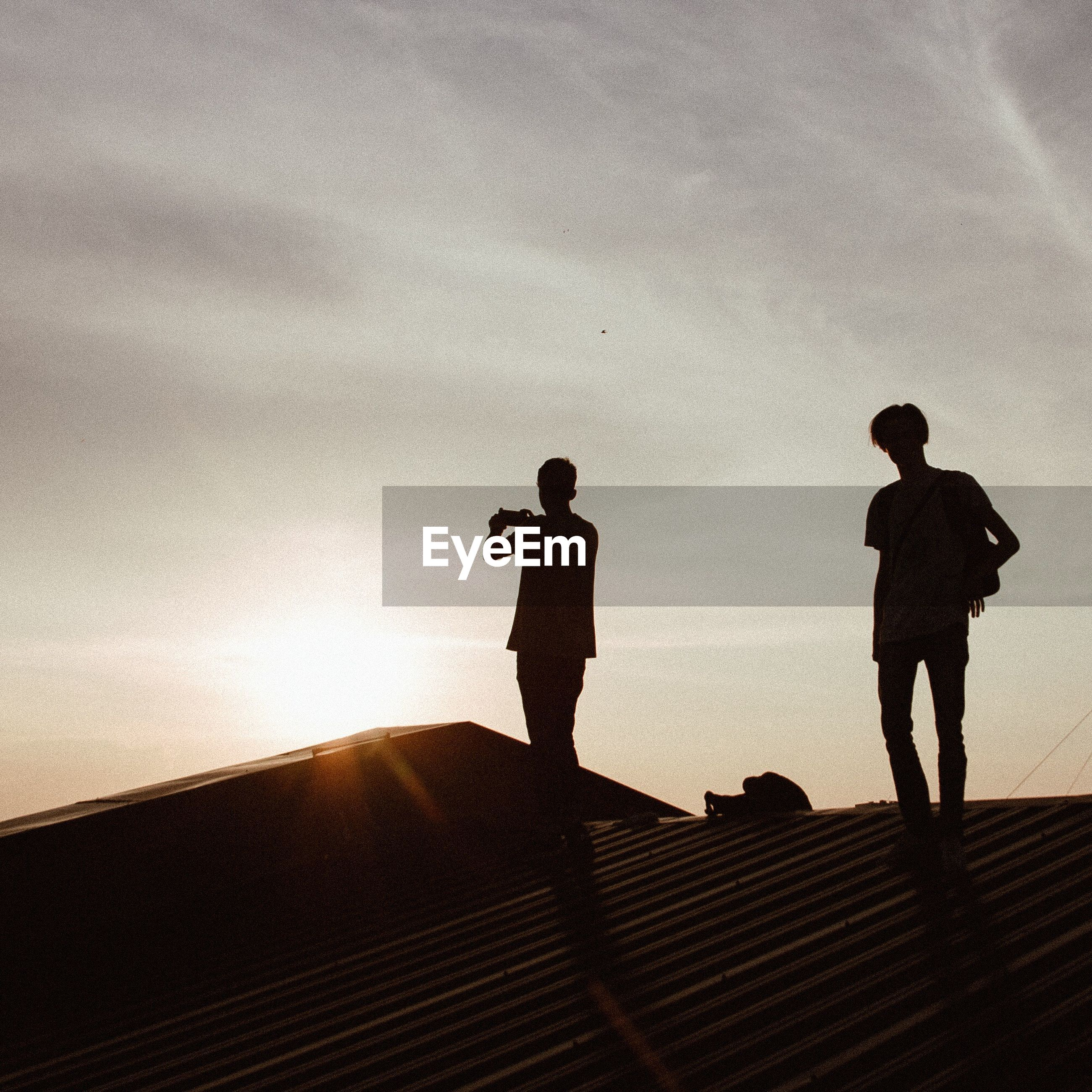 Silhouette friends on house roof against sky during sunset
