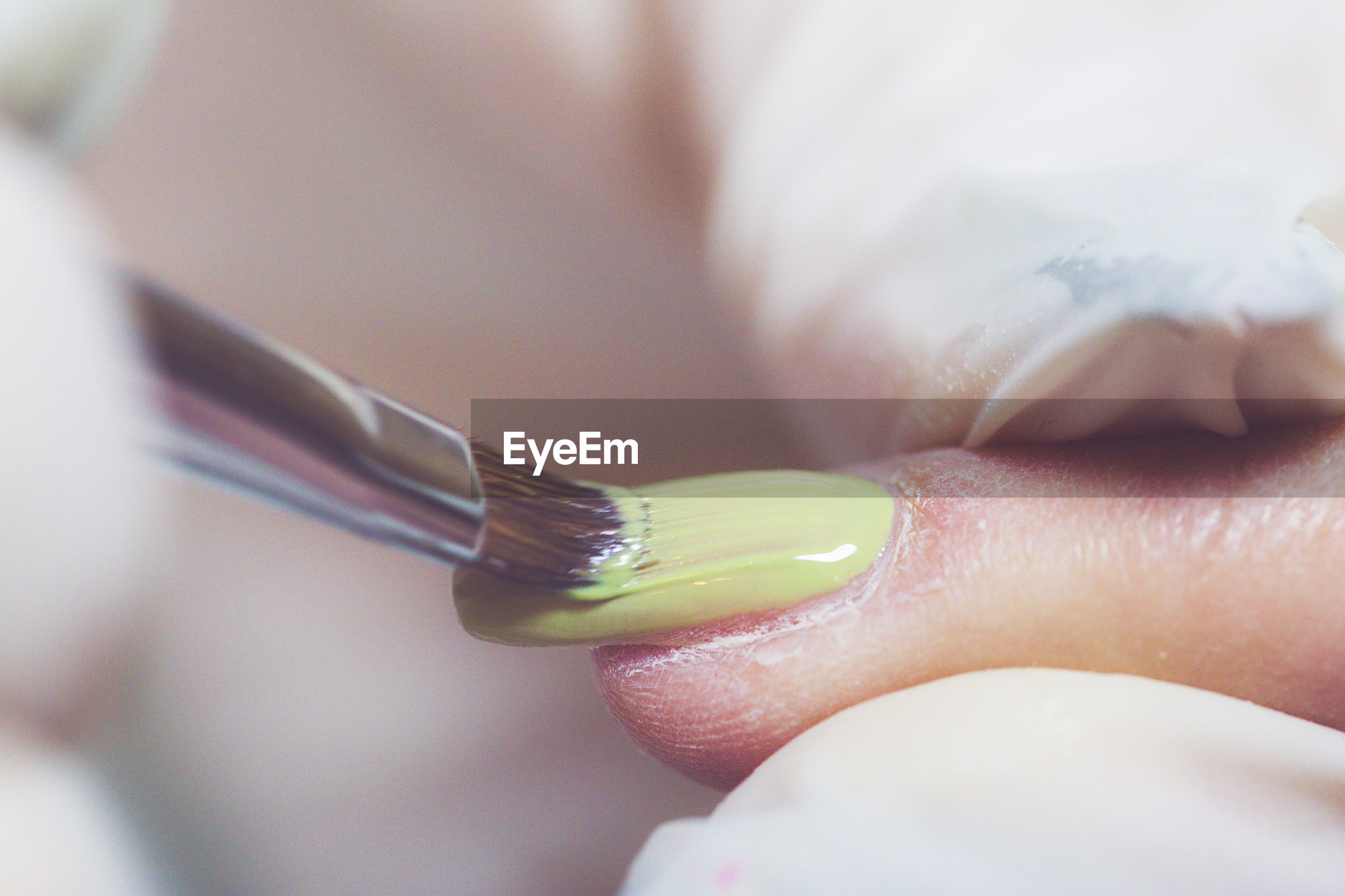 Cropped hand of beautician applying nail polish to woman
