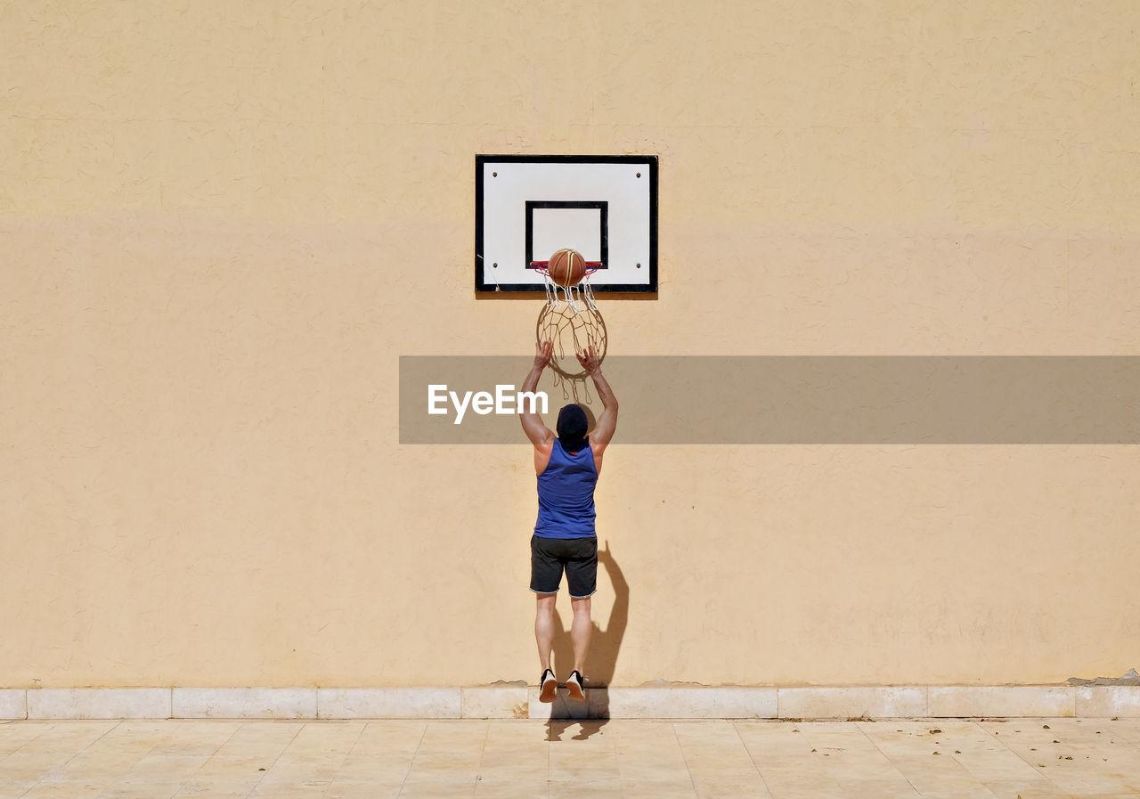 Full Length Of Man Jumping At Basketball Hoop