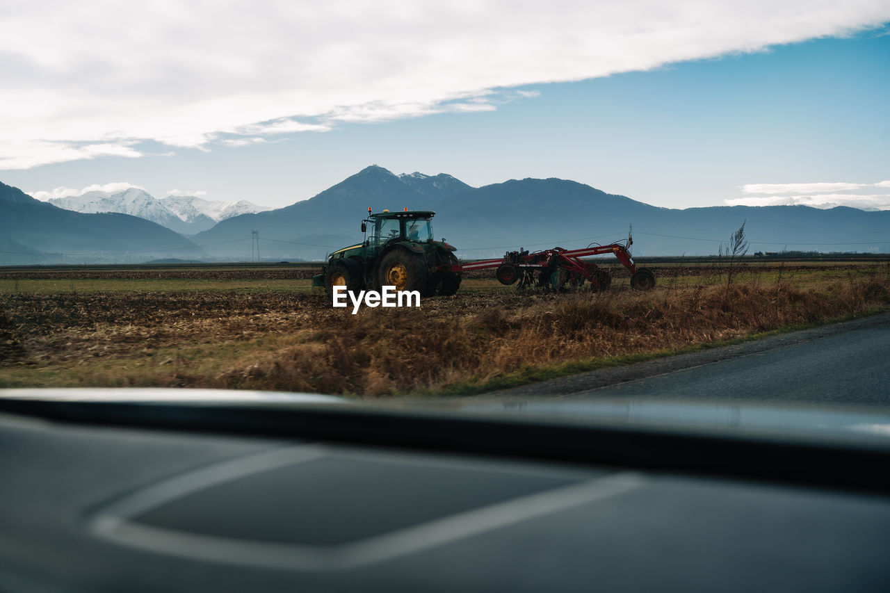 Vehicle on road by agricultural tractor on field against mountain lansdcape and sky during winter