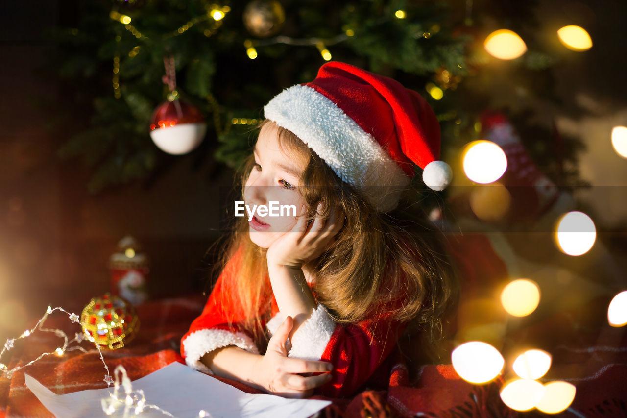 Cute girl lying down by illuminated christmas tree