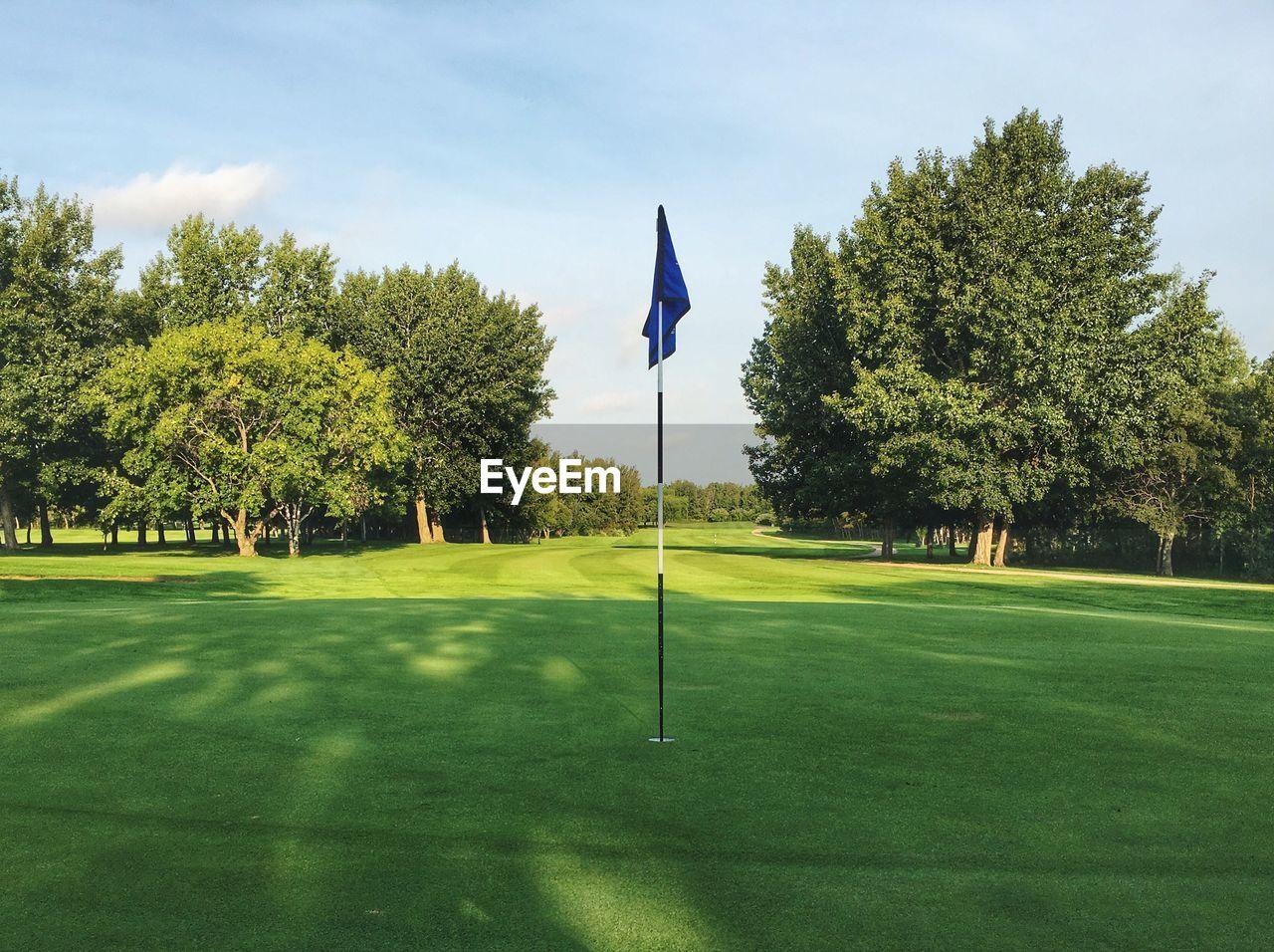 Flag On Golf Field Against Sky