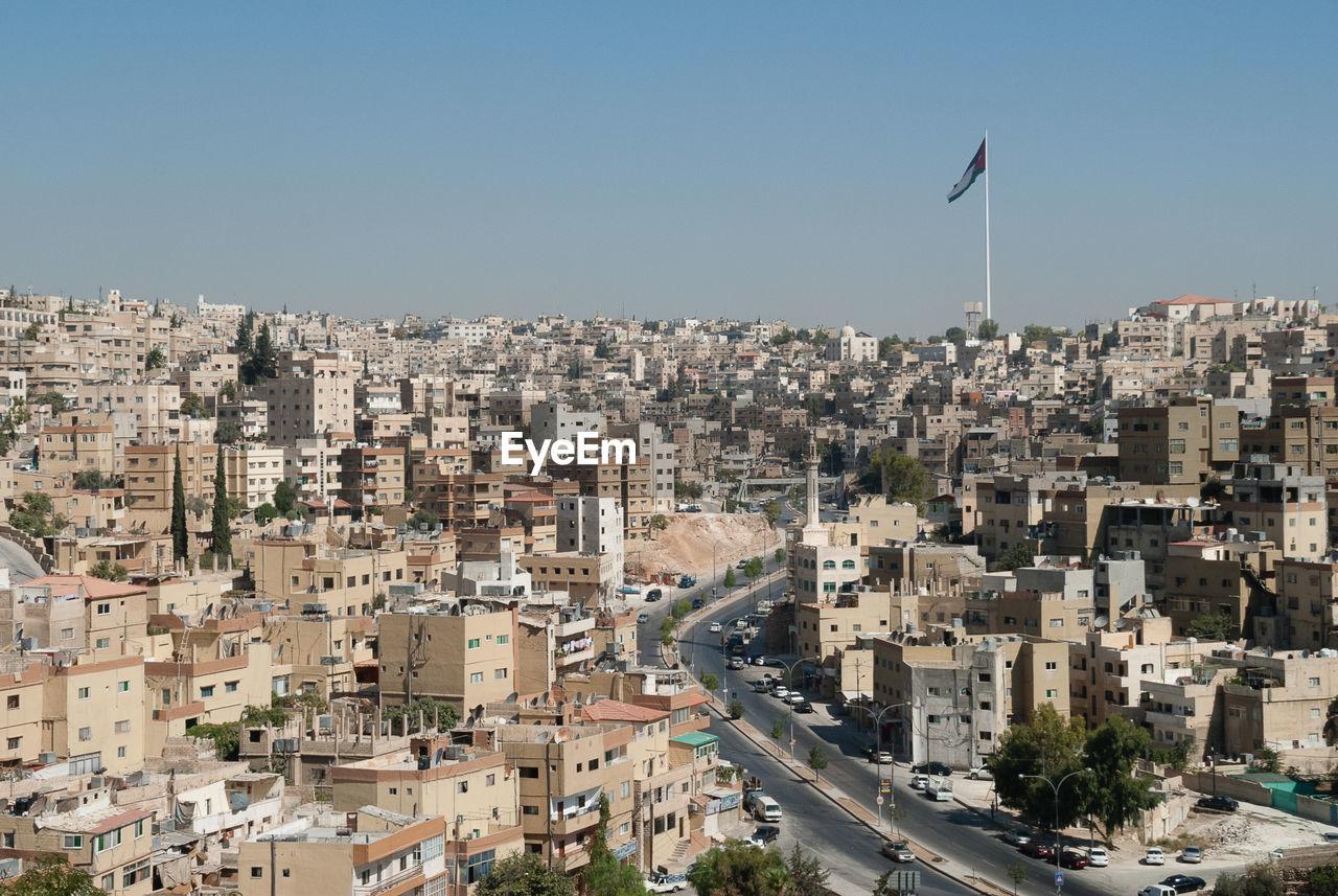 Large flag pole and flag and buildings in amman skyline, jordan