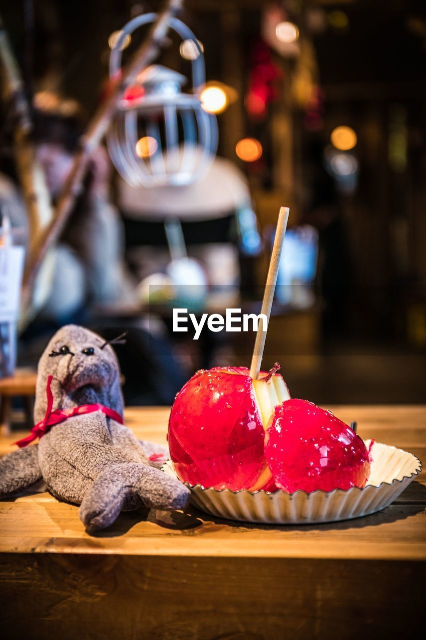 focus on foreground, food and drink, table, food, animal themes, no people, mammal, indoors, animal, freshness, close-up, one animal, sweet food, domestic, dog, canine, red, domestic animals, pets, ready-to-eat, temptation