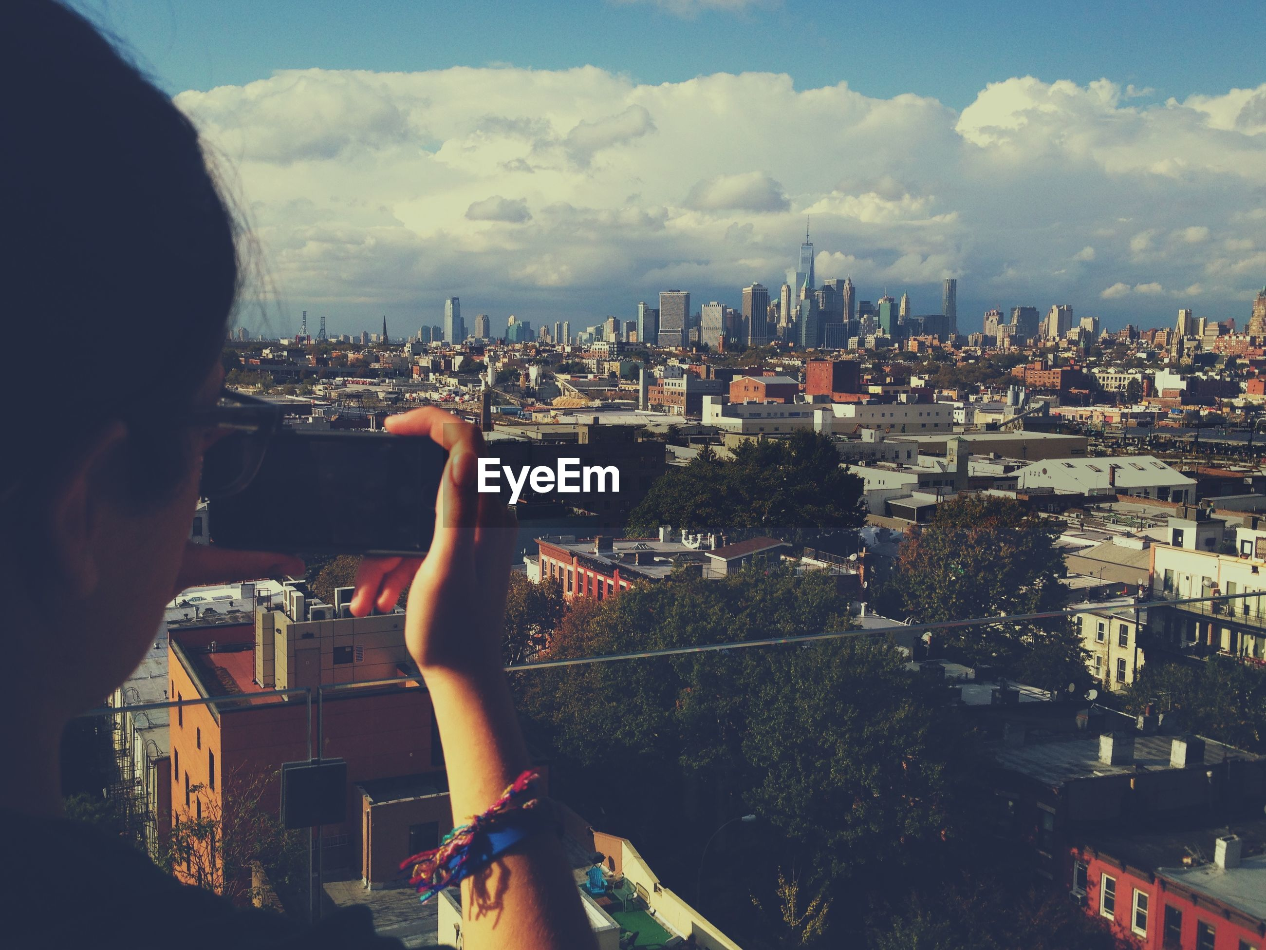 Woman photographing manhattan against sky