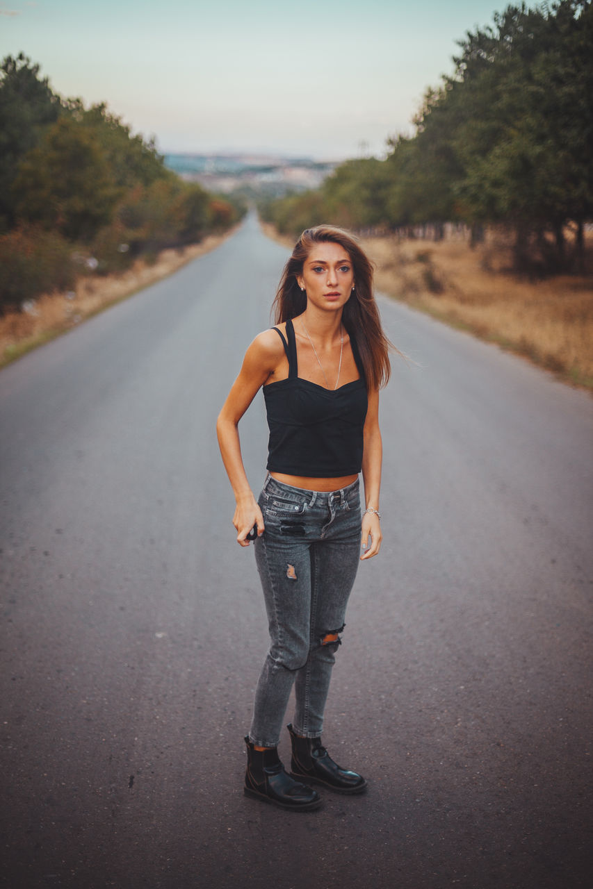 one person, portrait, road, young adult, standing, real people, full length, casual clothing, lifestyles, young women, front view, leisure activity, focus on foreground, transportation, looking at camera, direction, beauty, the way forward, beautiful woman, outdoors, diminishing perspective, hairstyle