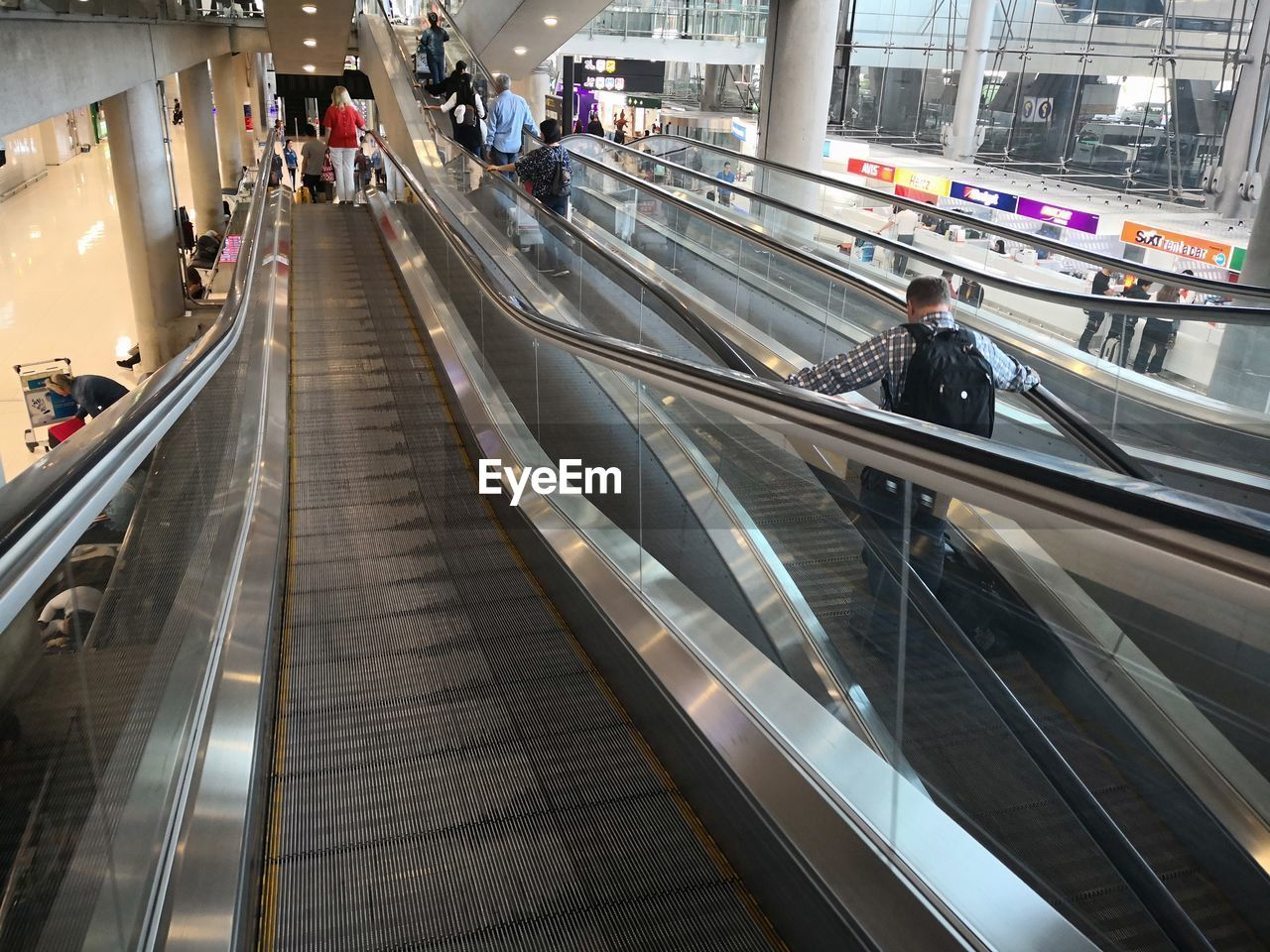 HIGH ANGLE VIEW OF PEOPLE MOVING ON ESCALATOR