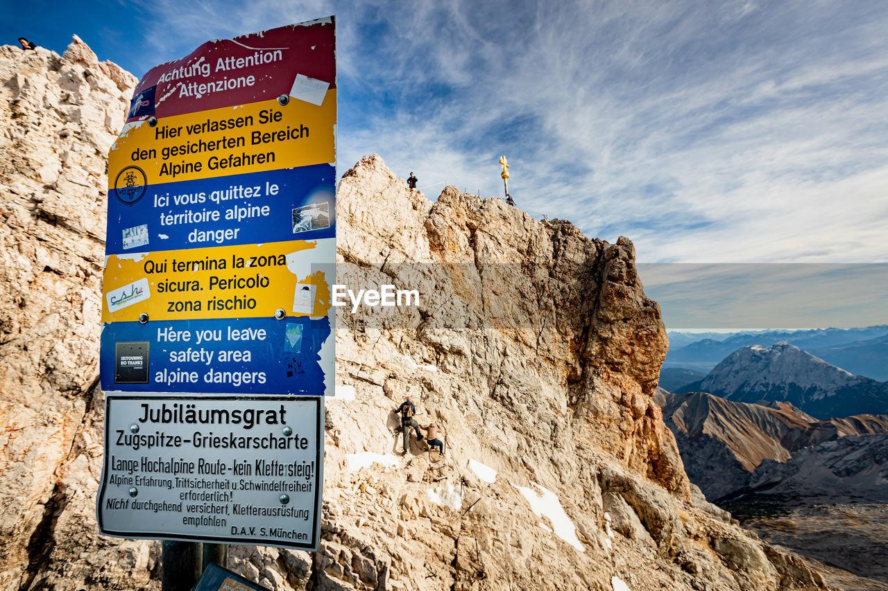 INFORMATION SIGN ON ROCKS AGAINST SKY
