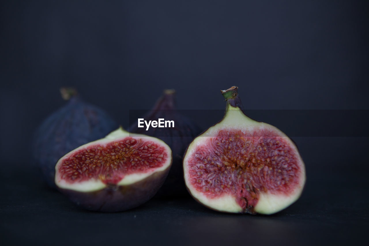 food and drink, fruit, freshness, healthy eating, food, wellbeing, still life, fig, studio shot, indoors, close-up, no people, cross section, slice, black background, group of objects, selective focus, three objects, table, ripe