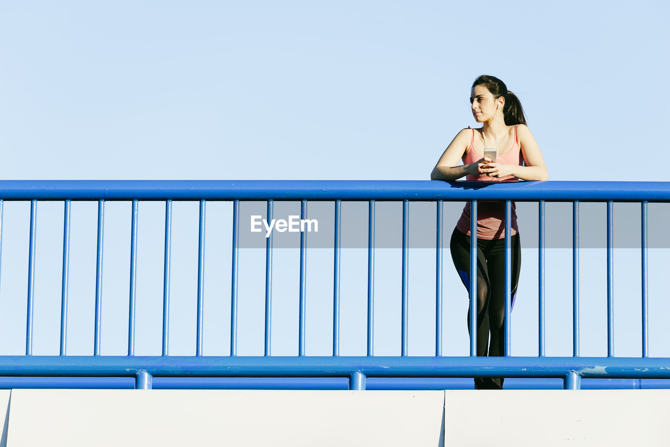 Low angle view of young woman using mobile phone while standing on footbridge against clear sky