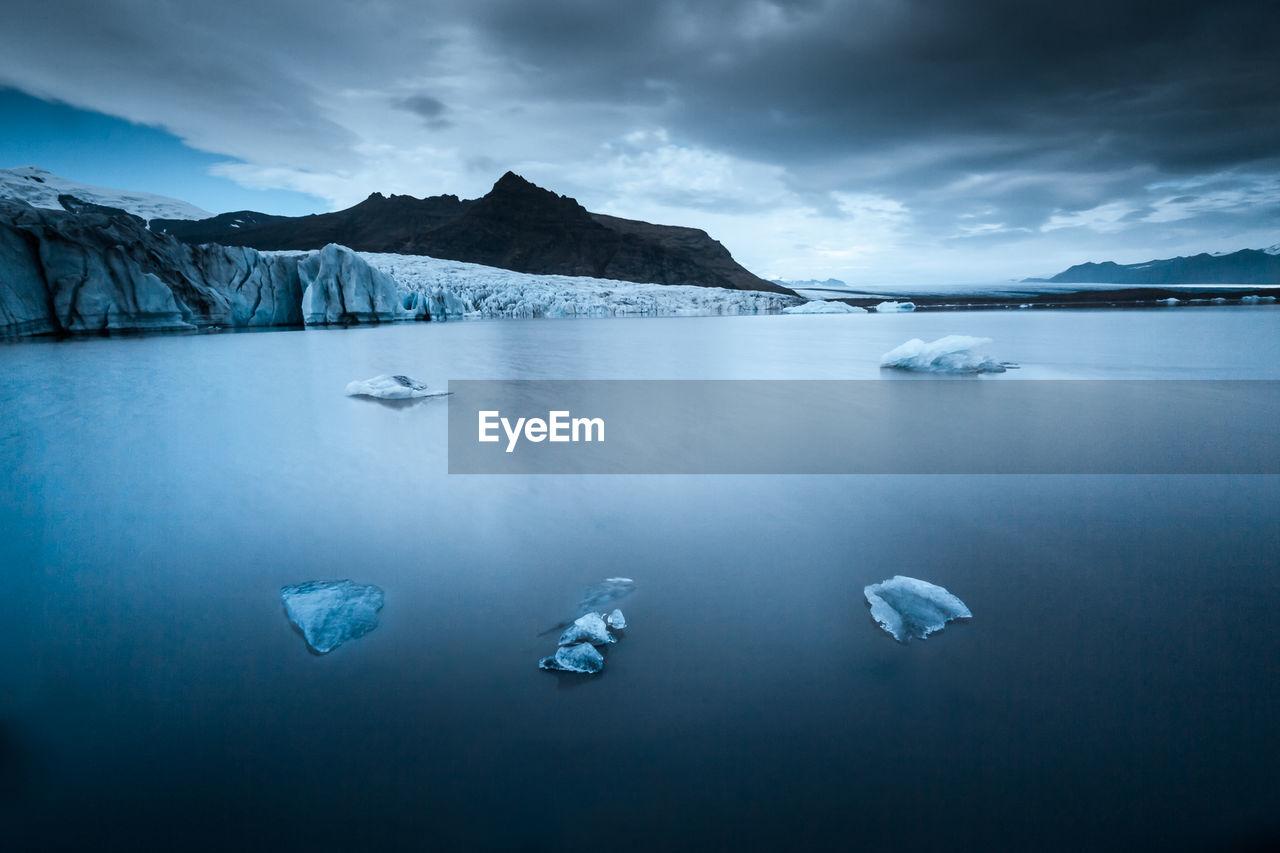 Iceberg floating in sea against sky at dusk