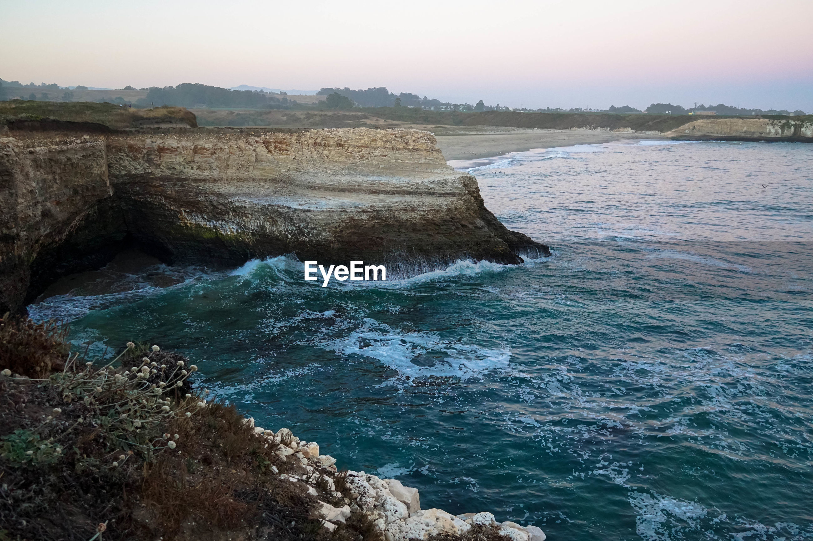 Scenic view of sea by rock formations during sunset