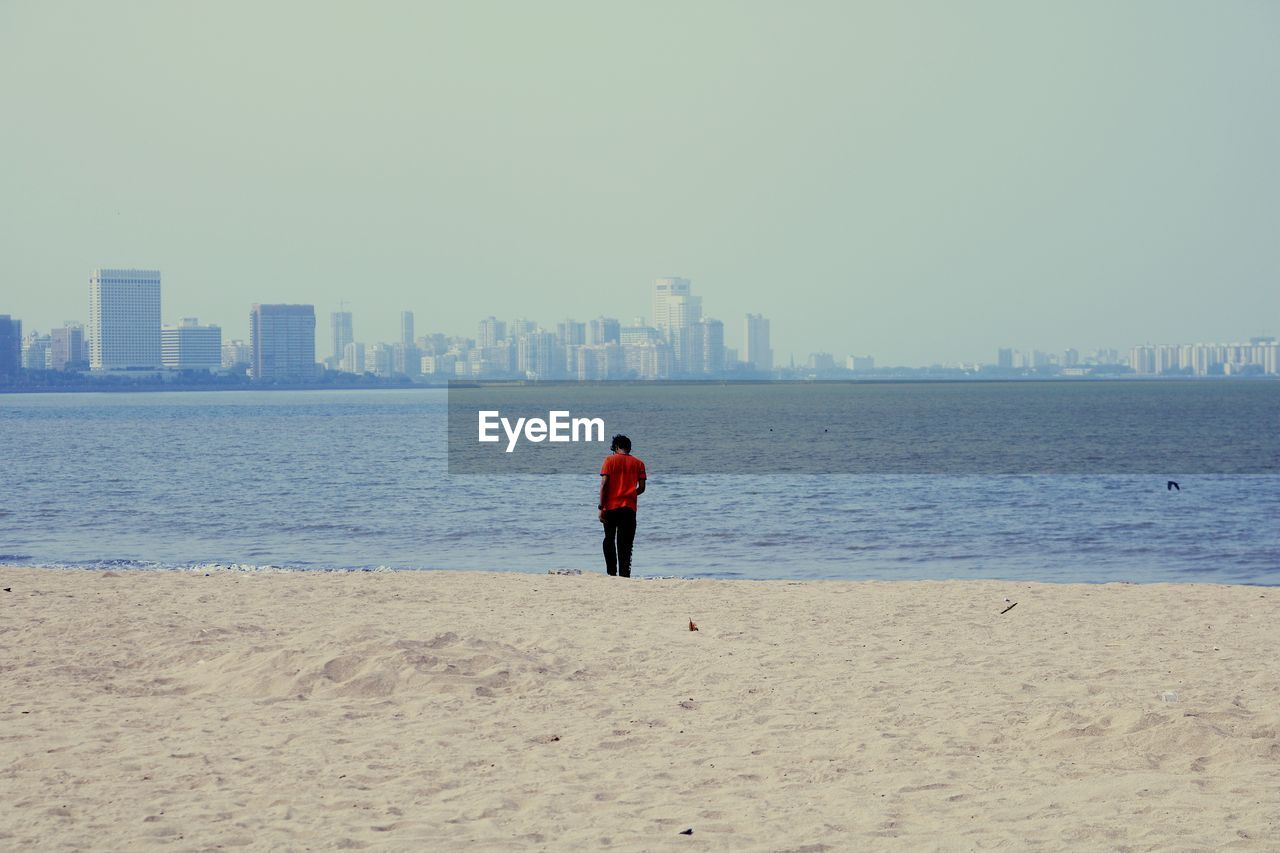 water, sky, sea, beach, building exterior, architecture, land, built structure, one person, real people, city, nature, rear view, sand, clear sky, full length, lifestyles, day, urban skyline, outdoors, office building exterior, skyscraper