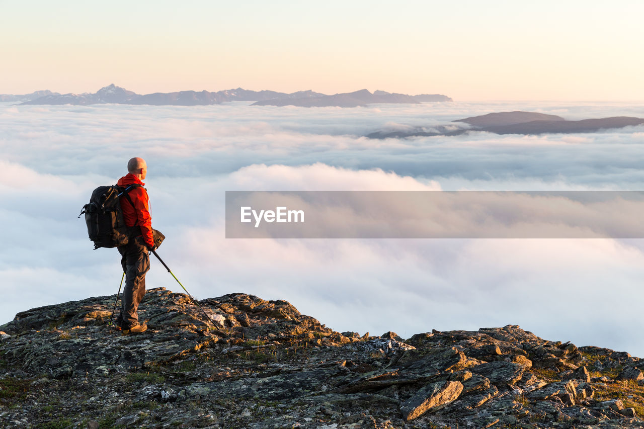 Side view of hiker standing on cliff against clouds