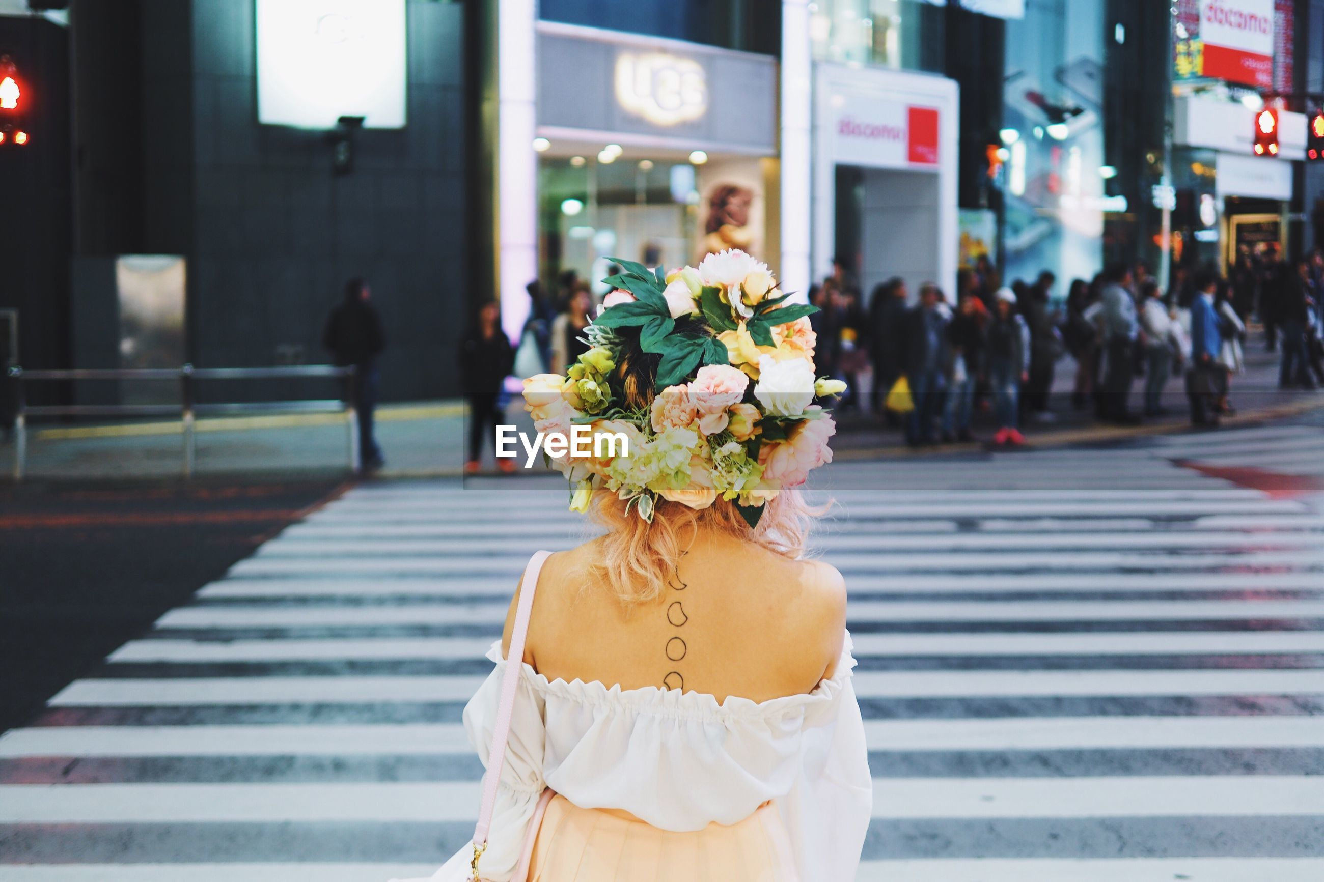 Rear view of a woman with flowers on head crossing road