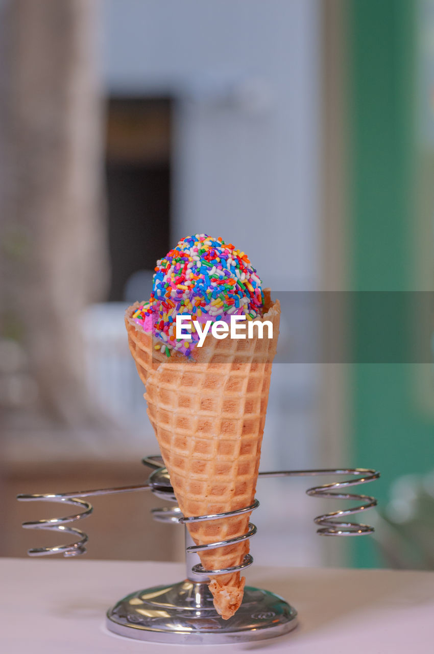 Close-up of ice cream cone with colorful sprinkles