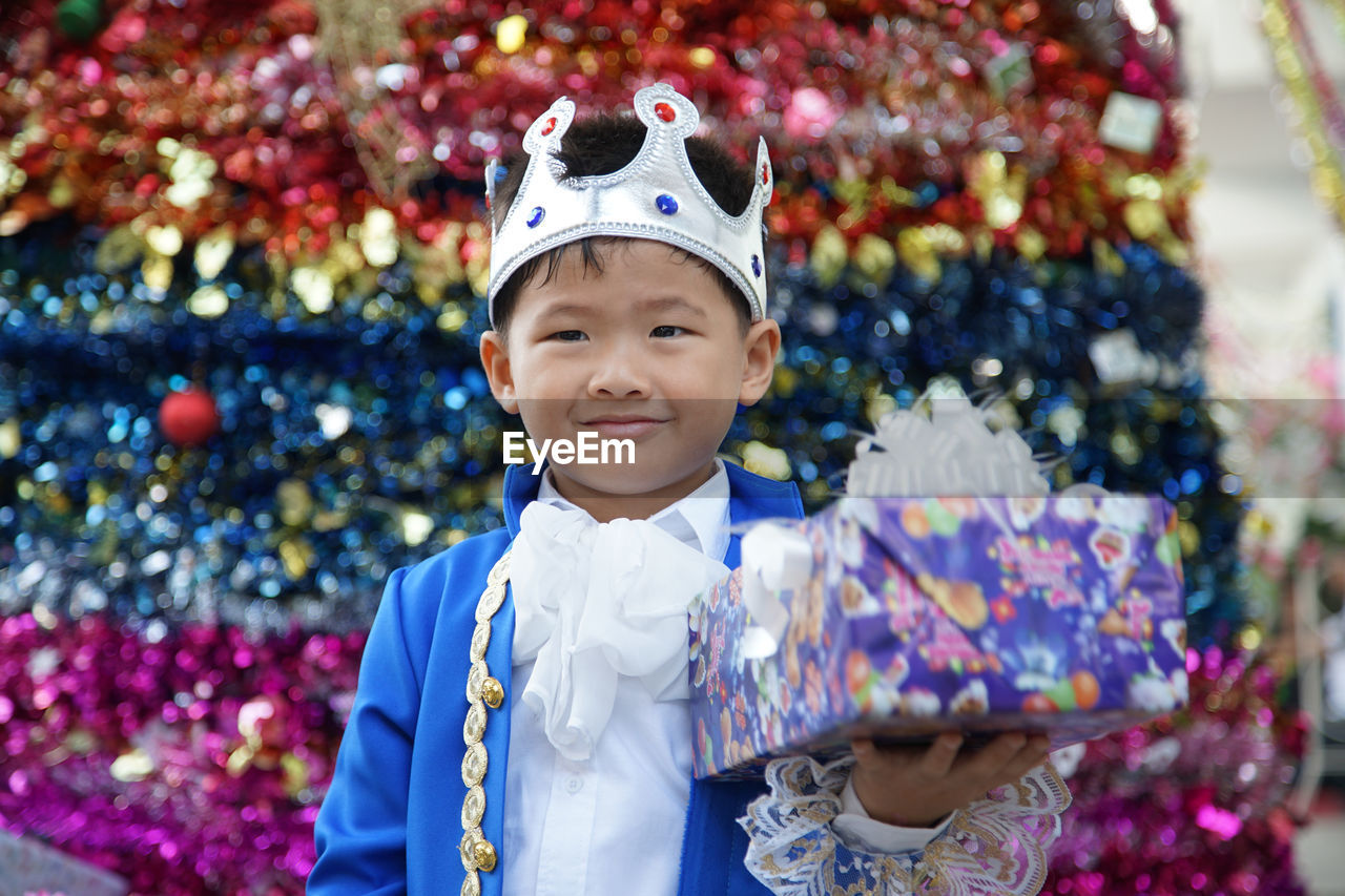 Smiling boy wearing crown holding gift box while standing in party