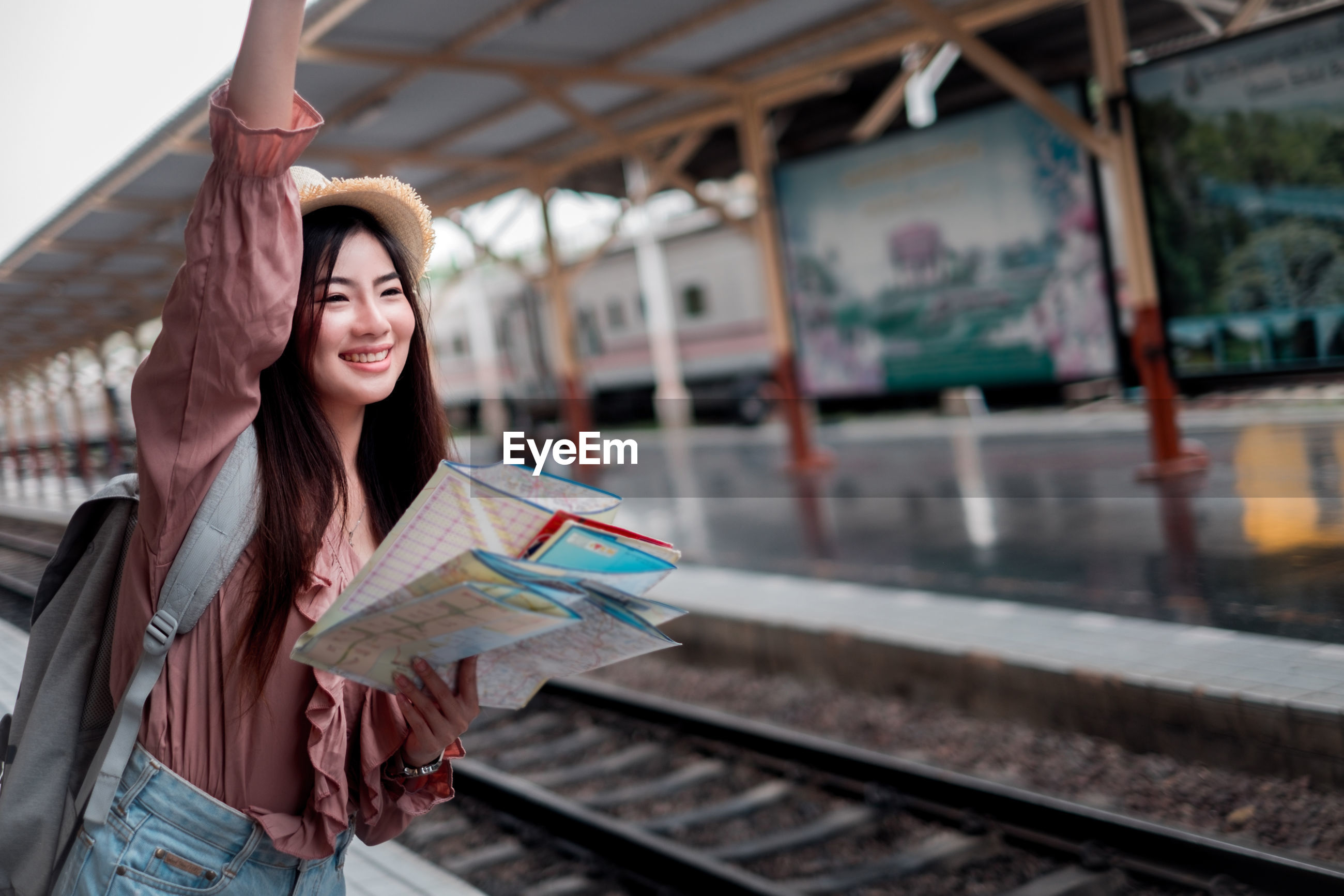 Smiling woman waving hand while standing with map at railroad station