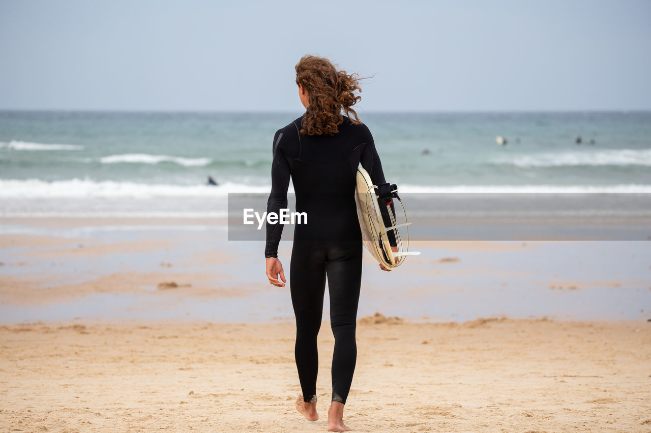 WOMAN STANDING AT BEACH AGAINST SKY