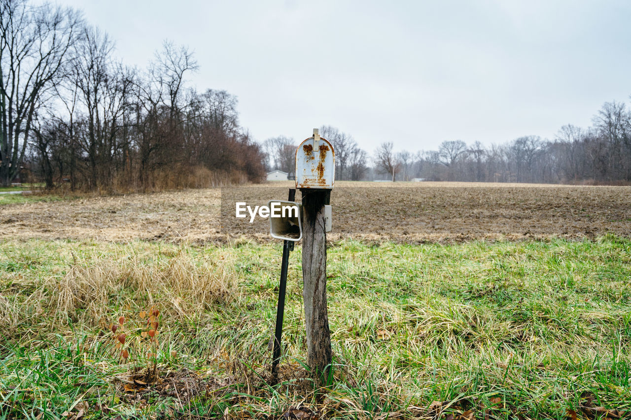 OLD WOODEN POST ON FIELD