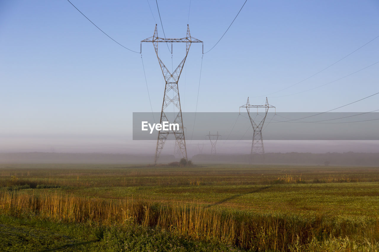 electricity, landscape, land, environment, field, sky, technology, cable, fuel and power generation, electricity pylon, power supply, power line, nature, plant, rural scene, no people, tranquility, connection, beauty in nature, tranquil scene, outdoors, electrical equipment