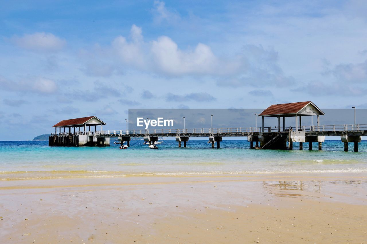 water, sea, beach, sky, sand, beauty in nature, nature, outdoors, tranquil scene, scenics, horizon over water, day, tranquility, stilt house, built structure, architecture, no people