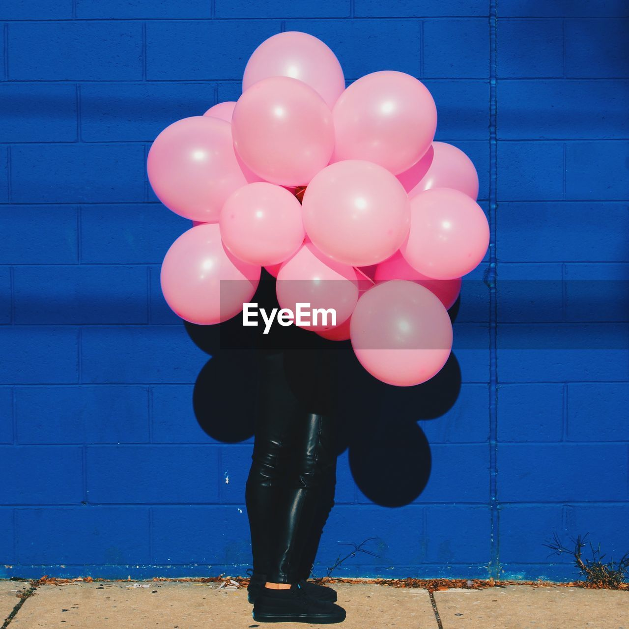 Person holding pink balloons in front of face