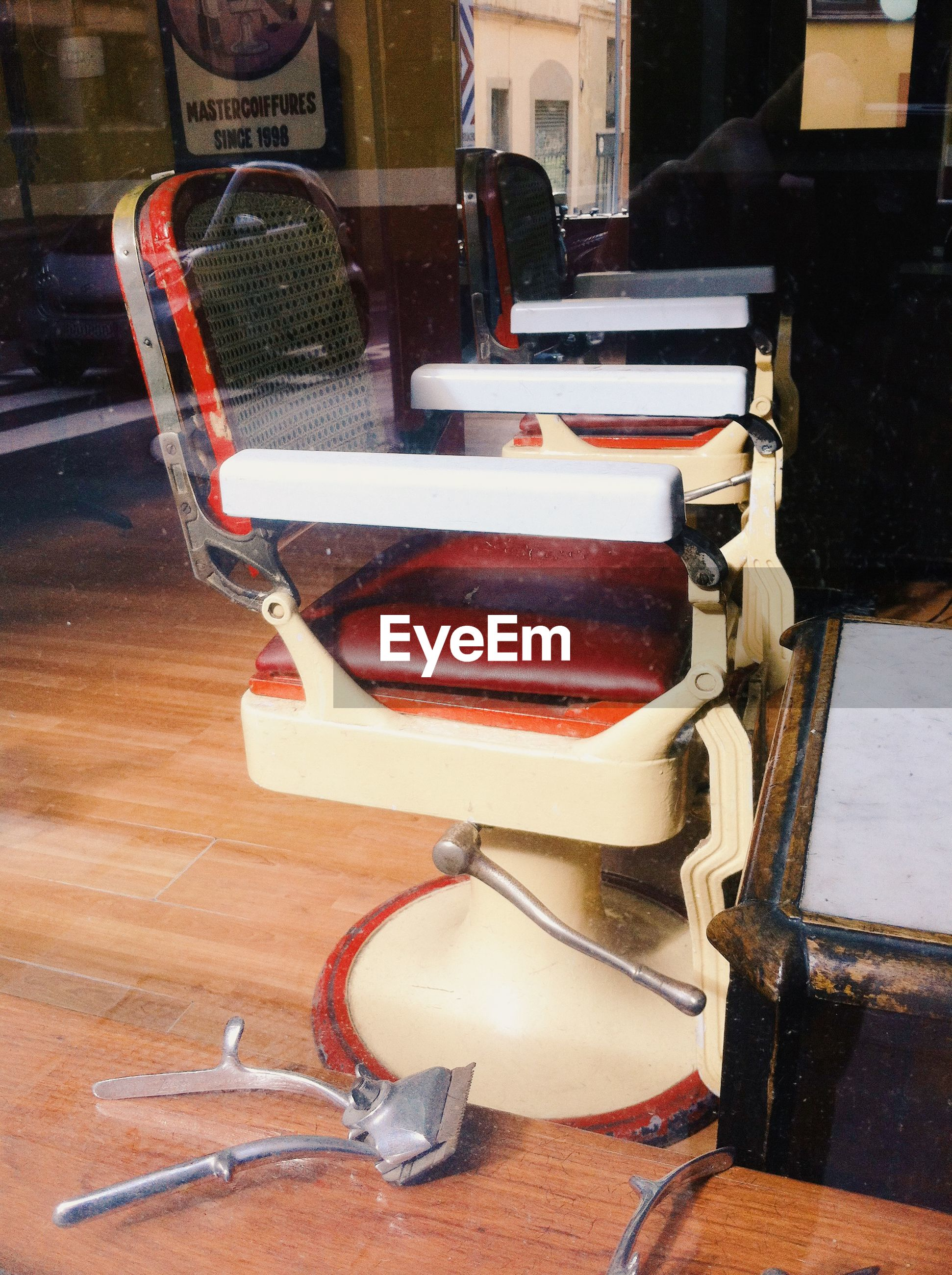 Chairs at barber shop seen through glass window