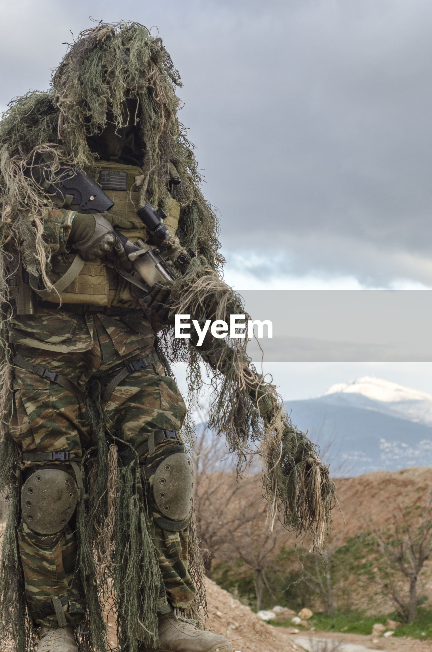 Army man in ghillie suit with rifle standing against cloudy sky