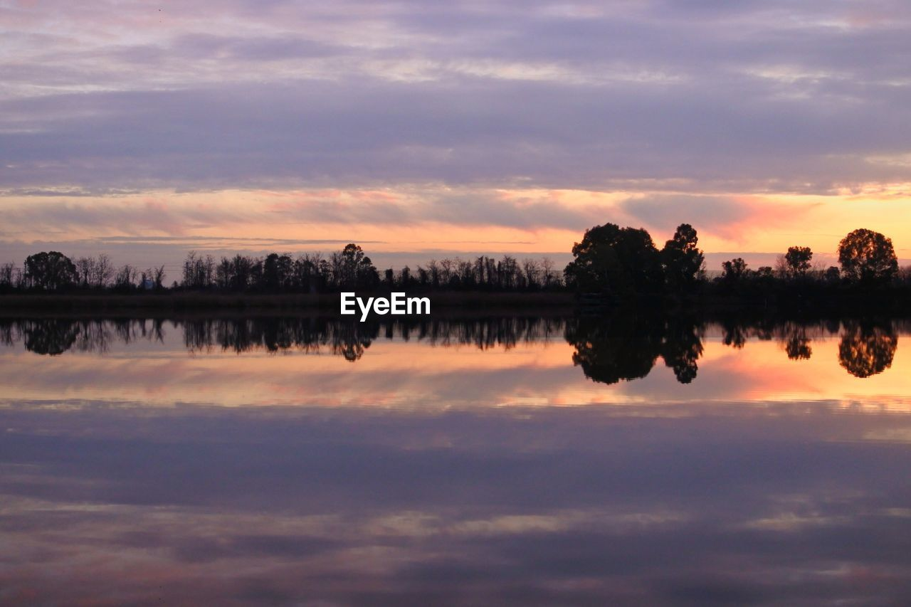 REFLECTION OF SILHOUETTE TREES IN LAKE AGAINST SKY AT SUNSET