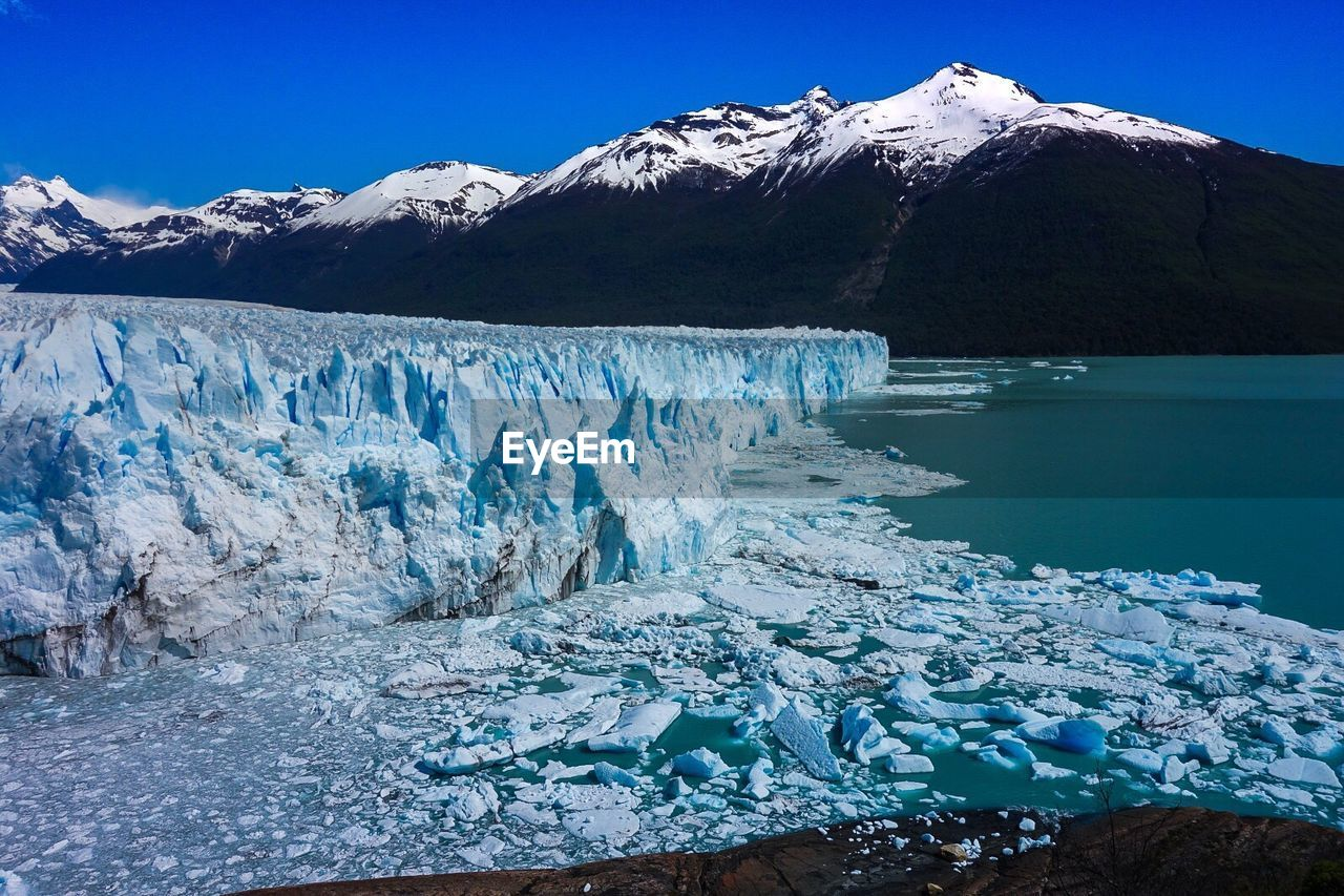 Scenic View Of Glaciers Melting With Snowcapped Mountain In Background