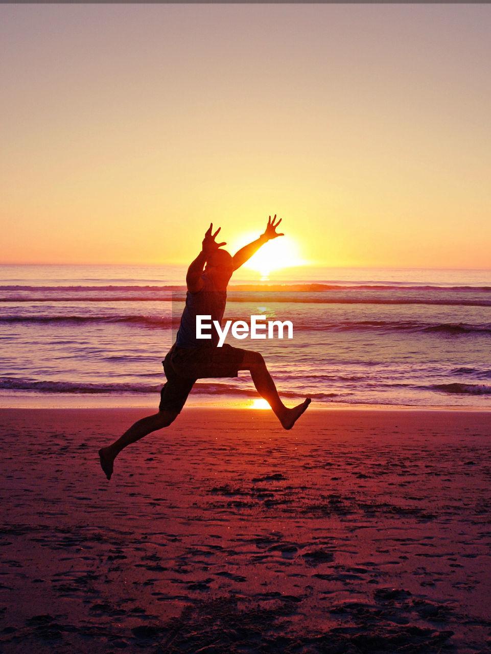 Man leaping into air against sun on beach