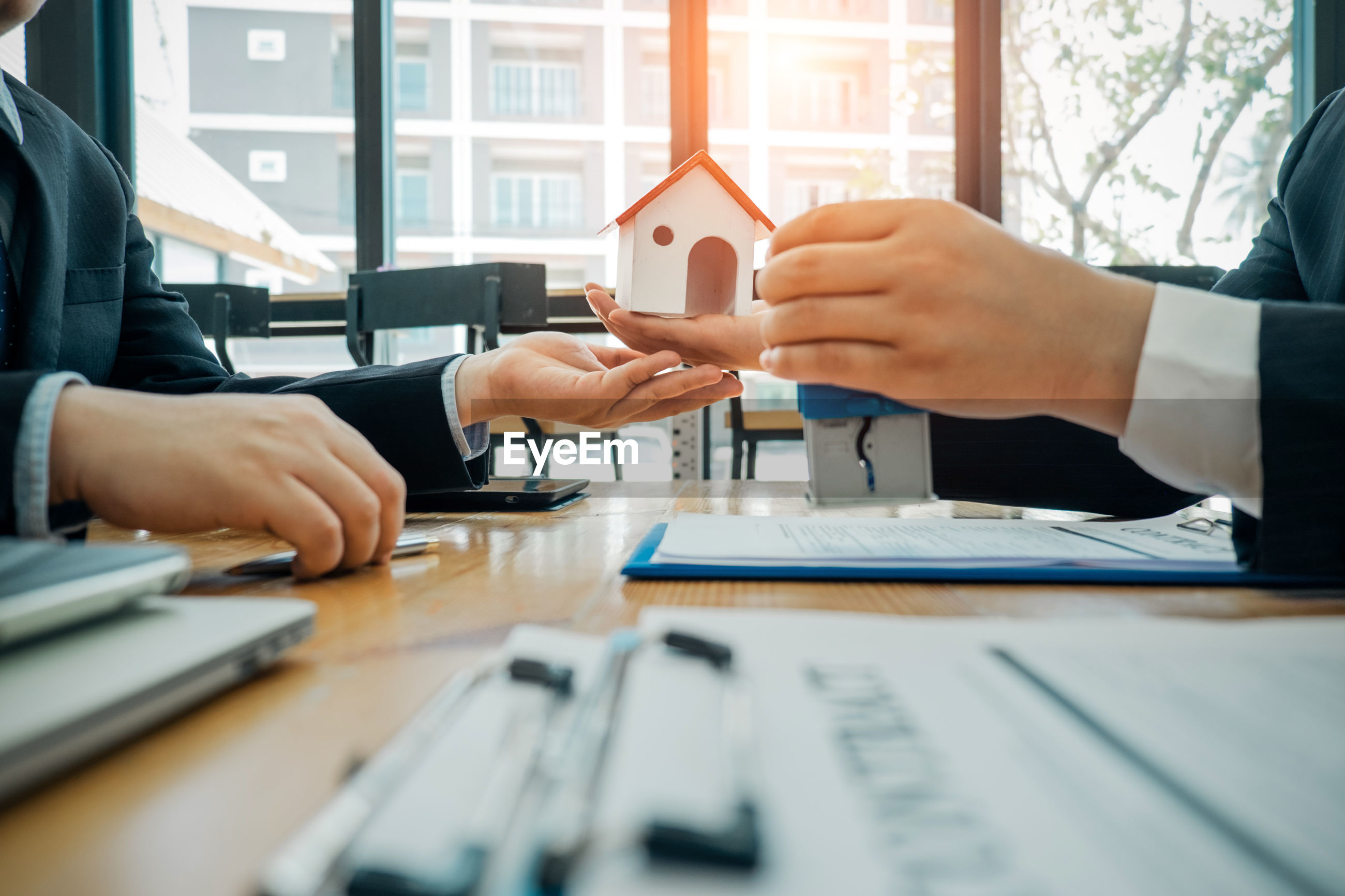 Midsection of businessman giving model home to colleague on table