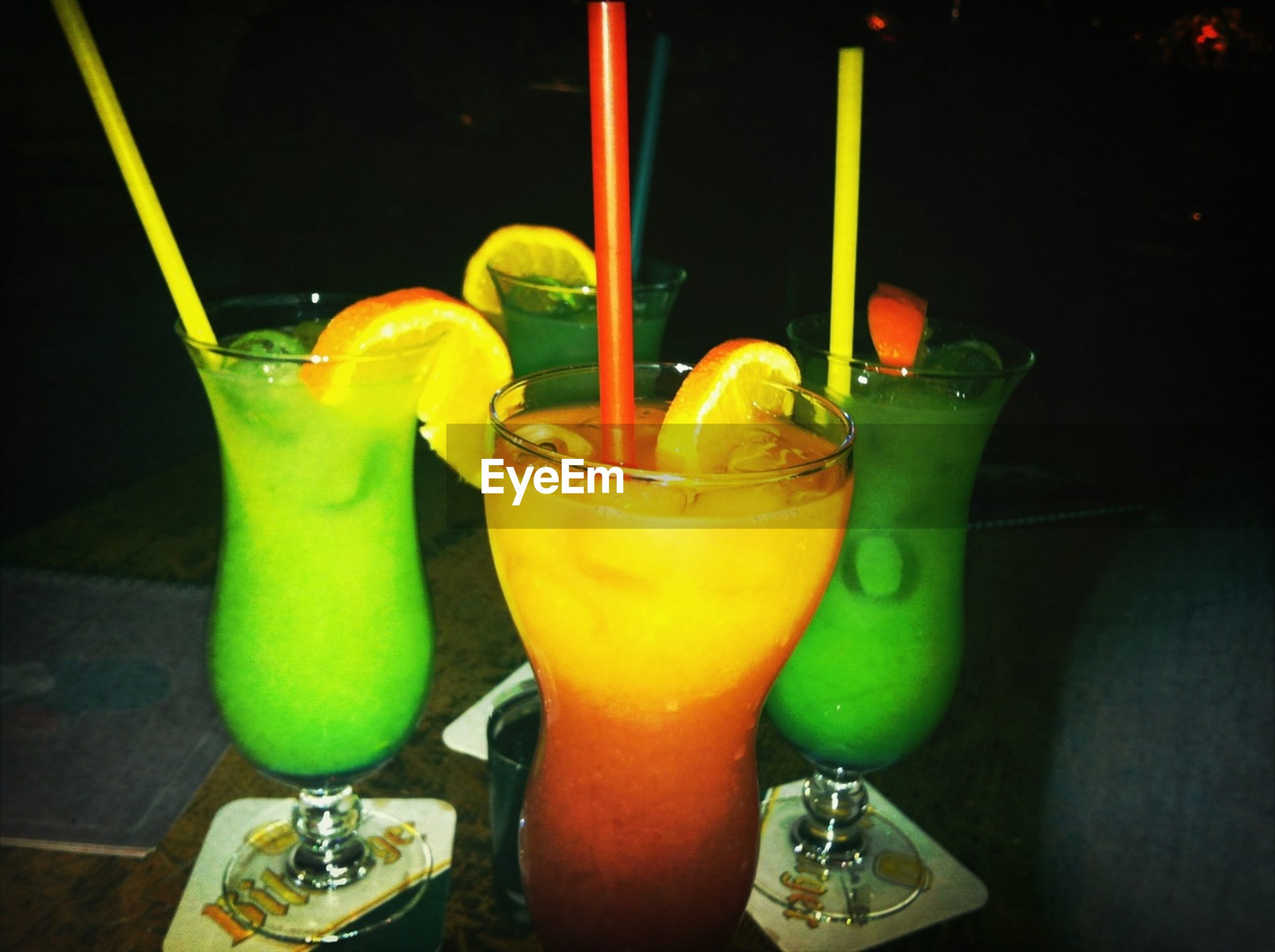 drink, indoors, food and drink, table, drinking glass, refreshment, still life, glass - material, freshness, yellow, close-up, drinking straw, alcohol, bottle, green color, glass, transparent, wineglass, juice, cocktail