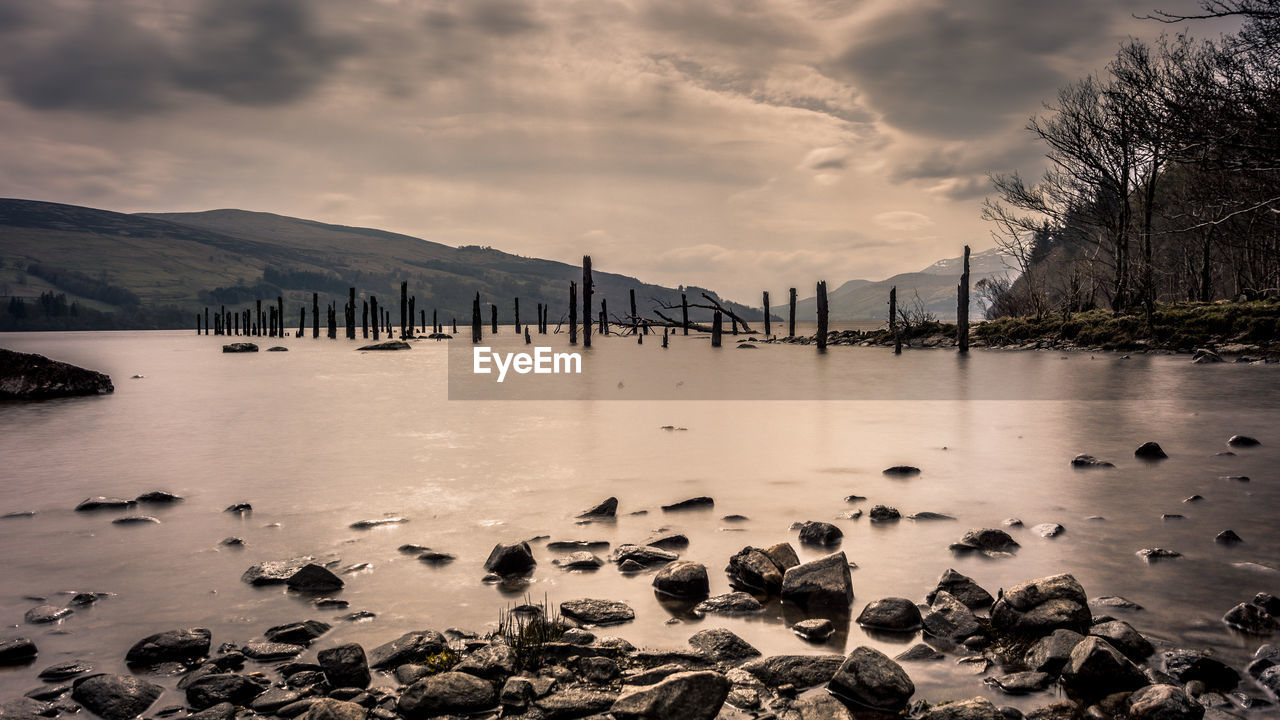water, sky, cloud - sky, nature, scenics - nature, beauty in nature, tranquil scene, tranquility, no people, rock, sunset, waterfront, rock - object, sea, non-urban scene, mountain, built structure, solid, wooden post