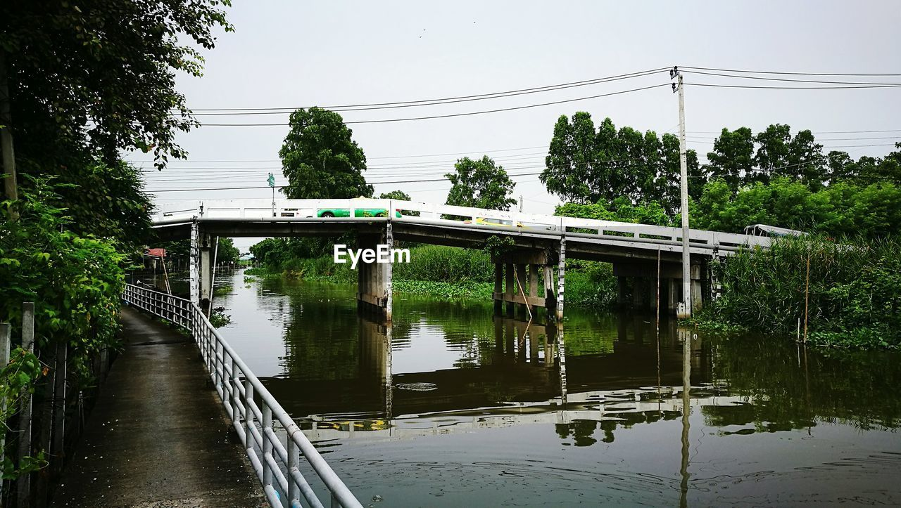 connection, water, bridge, bridge - man made structure, tree, transportation, built structure, architecture, plant, sky, nature, reflection, day, river, no people, cable, electricity, rail transportation, outdoors, architectural column