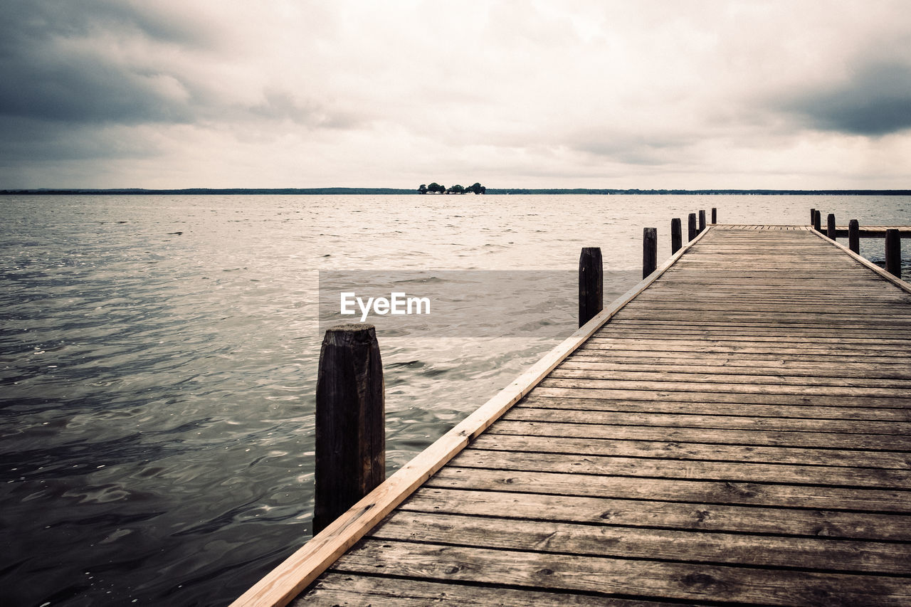 water, sky, cloud - sky, sea, pier, beauty in nature, wood - material, tranquility, tranquil scene, scenics - nature, nature, jetty, no people, day, horizon, post, horizon over water, outdoors, built structure, wooden post, wood paneling, long, groyne