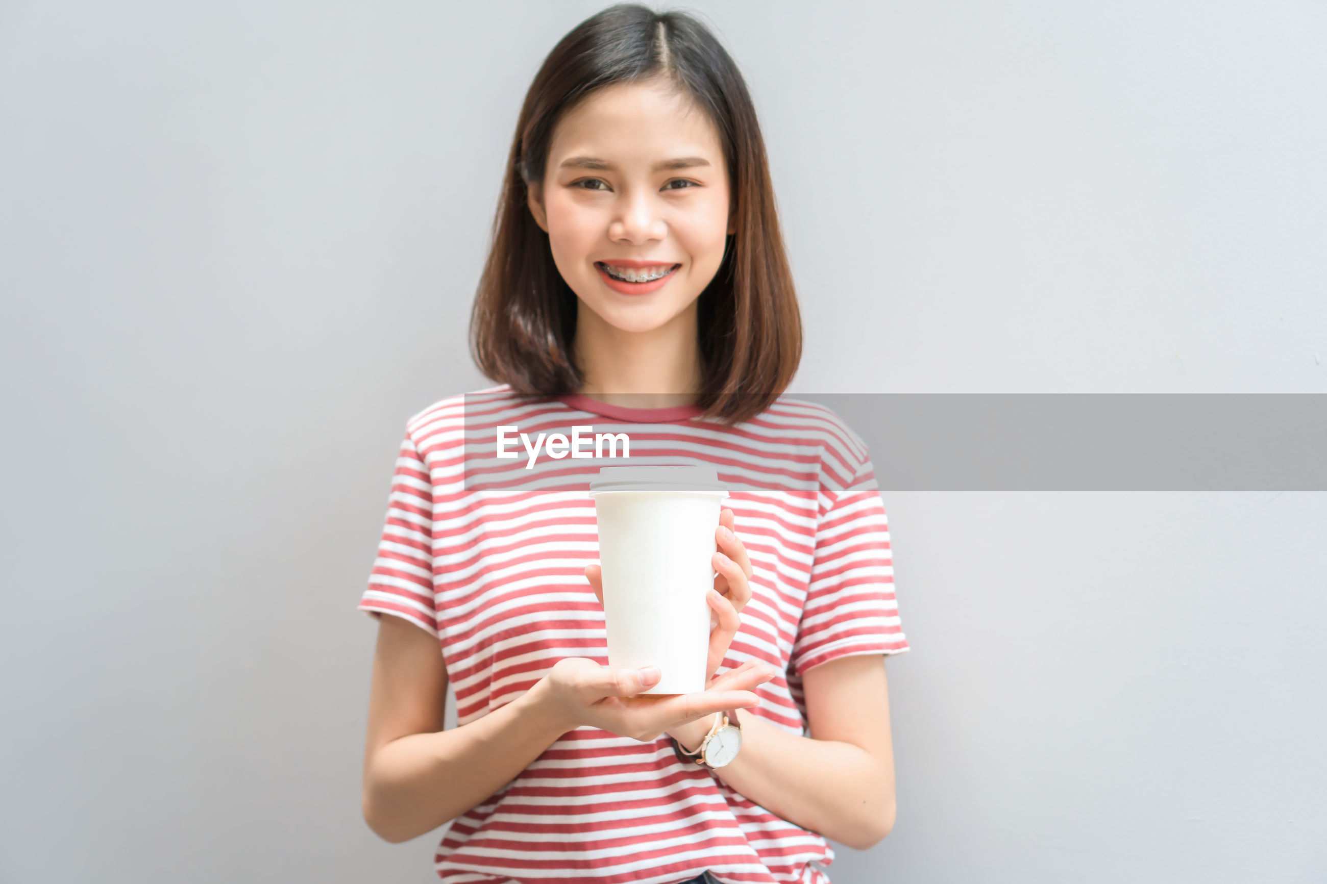 Portrait of smiling girl holding disposable cup against gray background