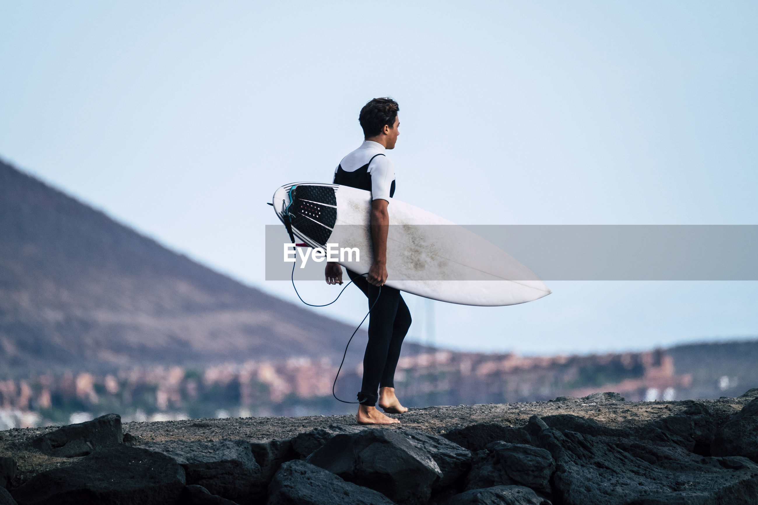 Teenage boy holding surfboard while standing on rock against clear sky