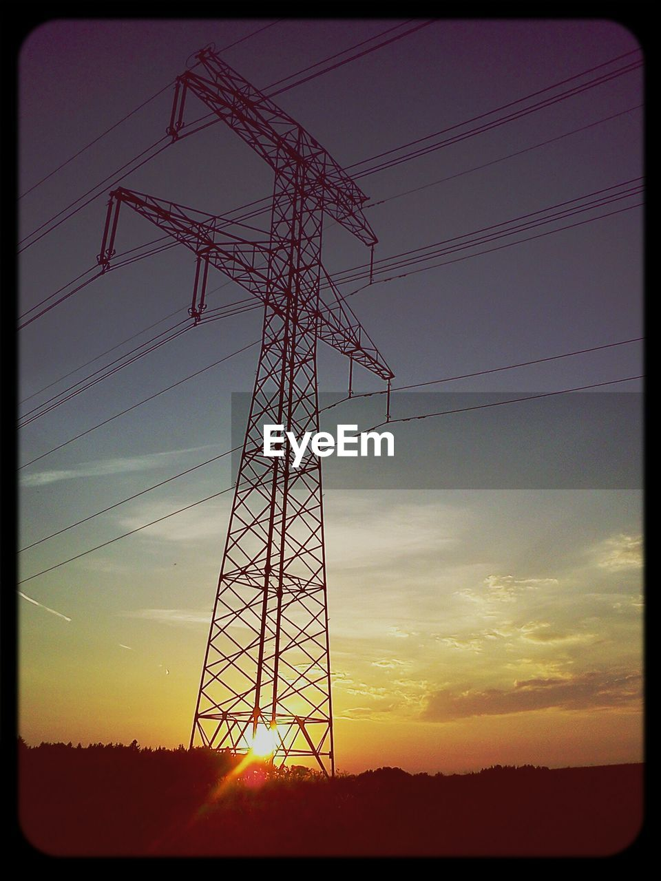 Low angle view of electricity pylon in field against sunset