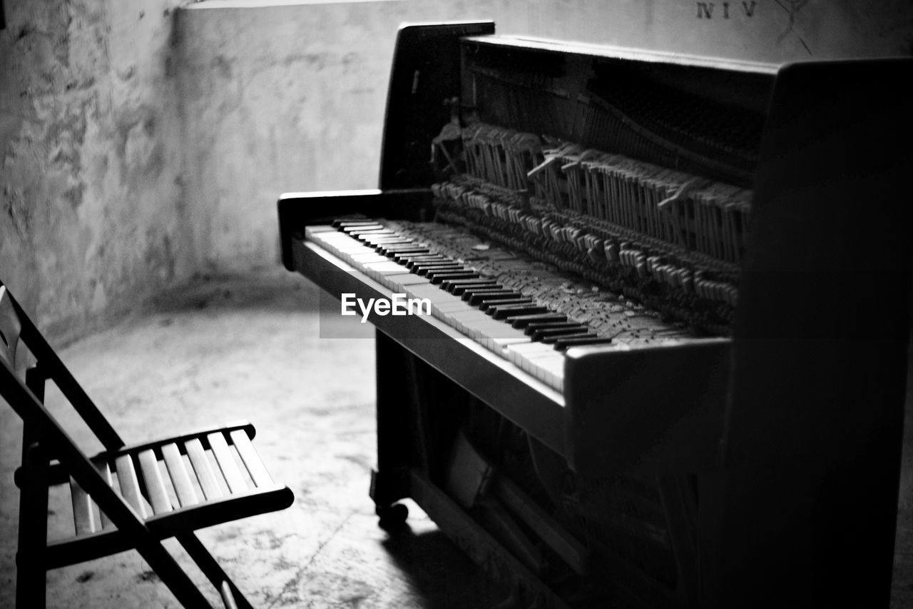 piano, musical instrument, musical equipment, music, indoors, piano key, arts culture and entertainment, no people, absence, keyboard instrument, home interior, keyboard, selective focus, seat, high angle view, technology, close-up, still life, chair, grand piano, antique