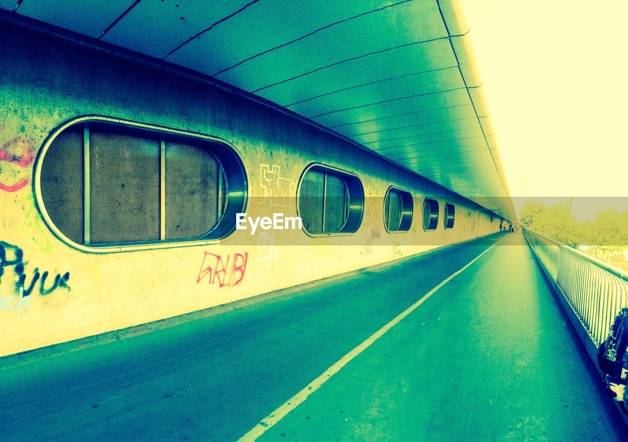 transportation, text, the way forward, diminishing perspective, western script, graffiti, blue, road, architecture, built structure, road marking, mode of transport, communication, vanishing point, rail transportation, no people, day, sky, land vehicle, empty