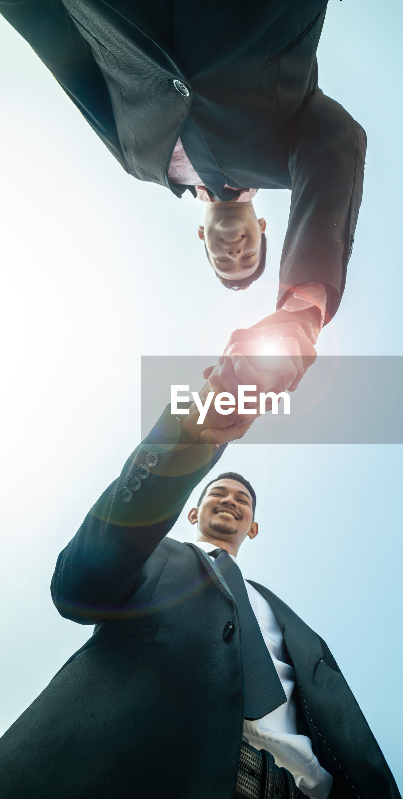 Directly below shot of businessmen shaking hands while standing against sky