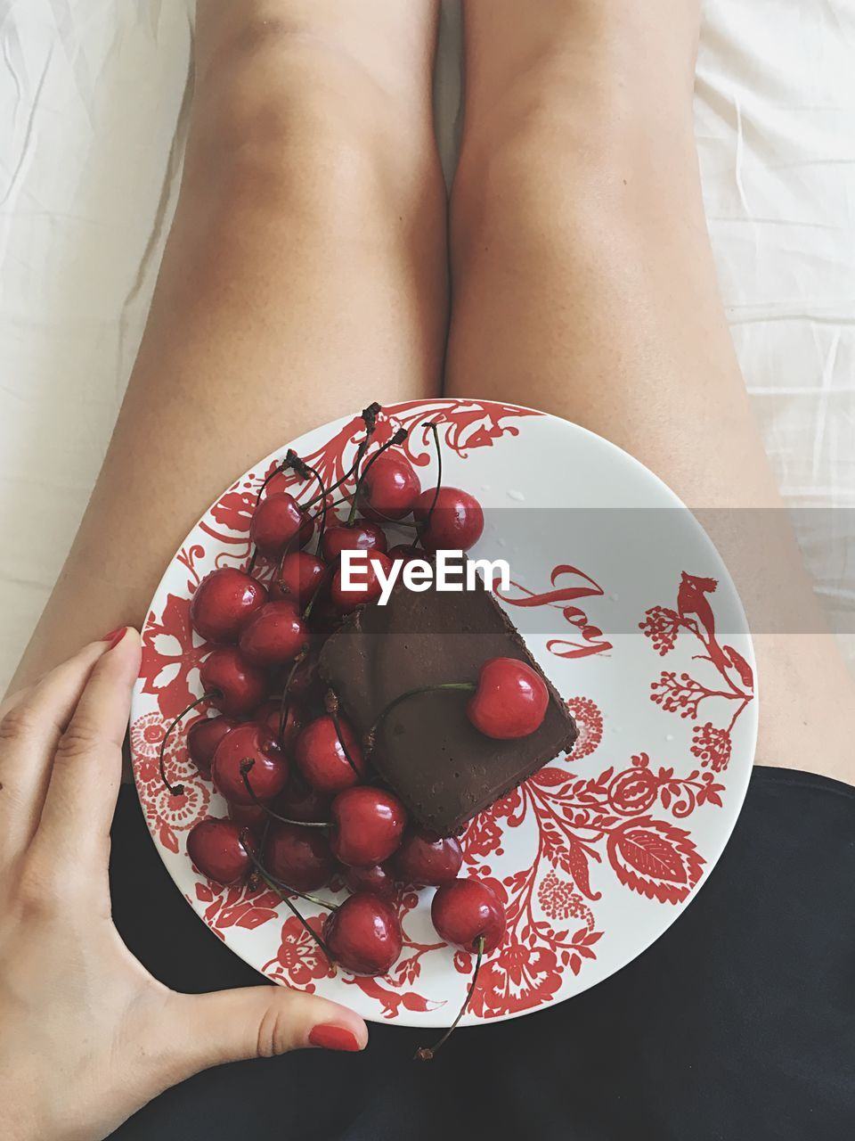 Midsection Of Woman Holding Chocolate Cake With Cherries In Plate On Bed