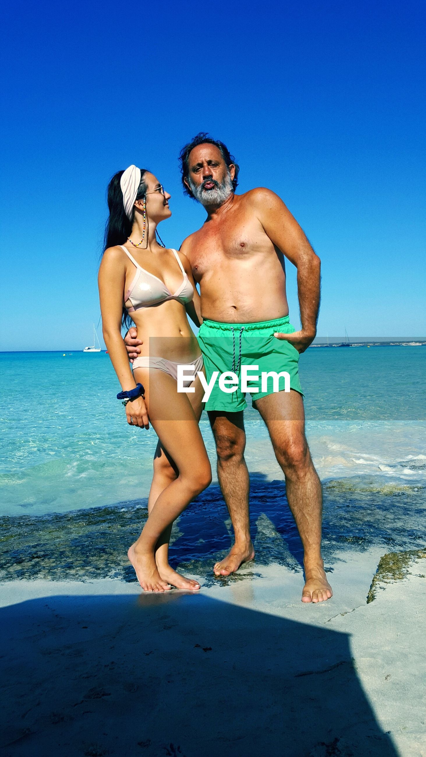 two people, sea, togetherness, full length, real people, standing, beach, love, shirtless, leisure activity, clear sky, nature, young women, young adult, men, day, young men, bikini, blue, water, beauty in nature, horizon over water, lifestyles, bonding, vacations, outdoors, scenics, sky, adult, people, adults only