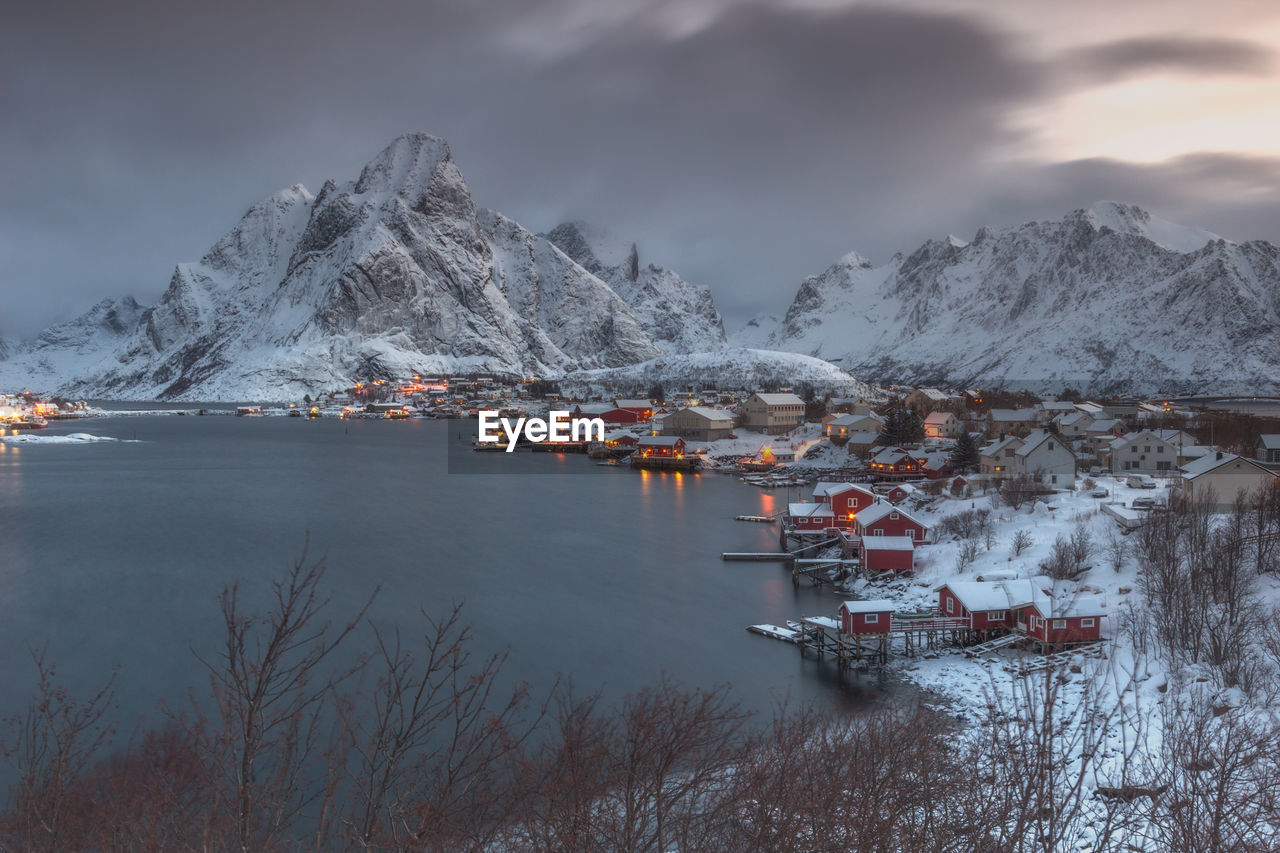 Scenic View Of Houses By Lake At Snowcapped Mountains