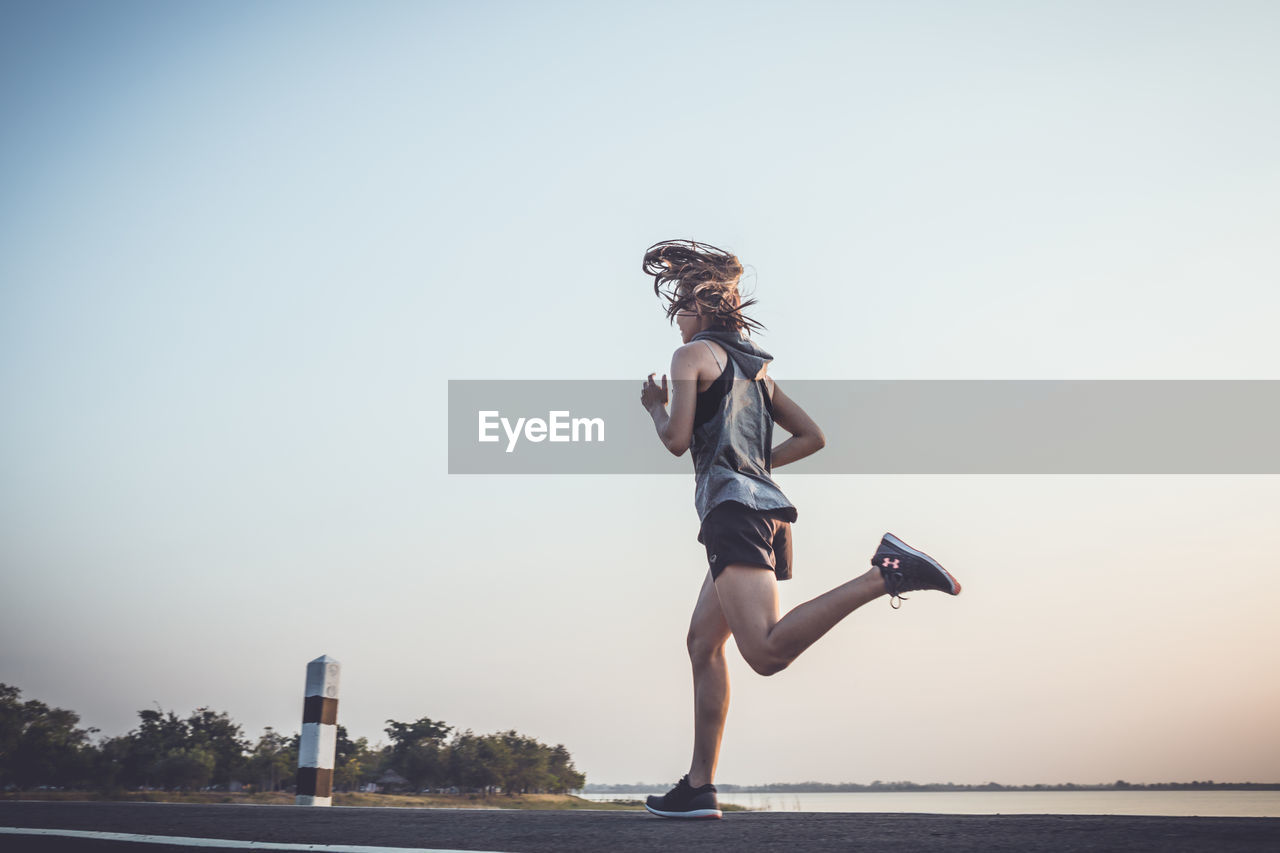 sky, full length, one person, lifestyles, real people, clear sky, leisure activity, young adult, nature, copy space, young women, side view, water, beauty in nature, running, women, females, effort, outdoors